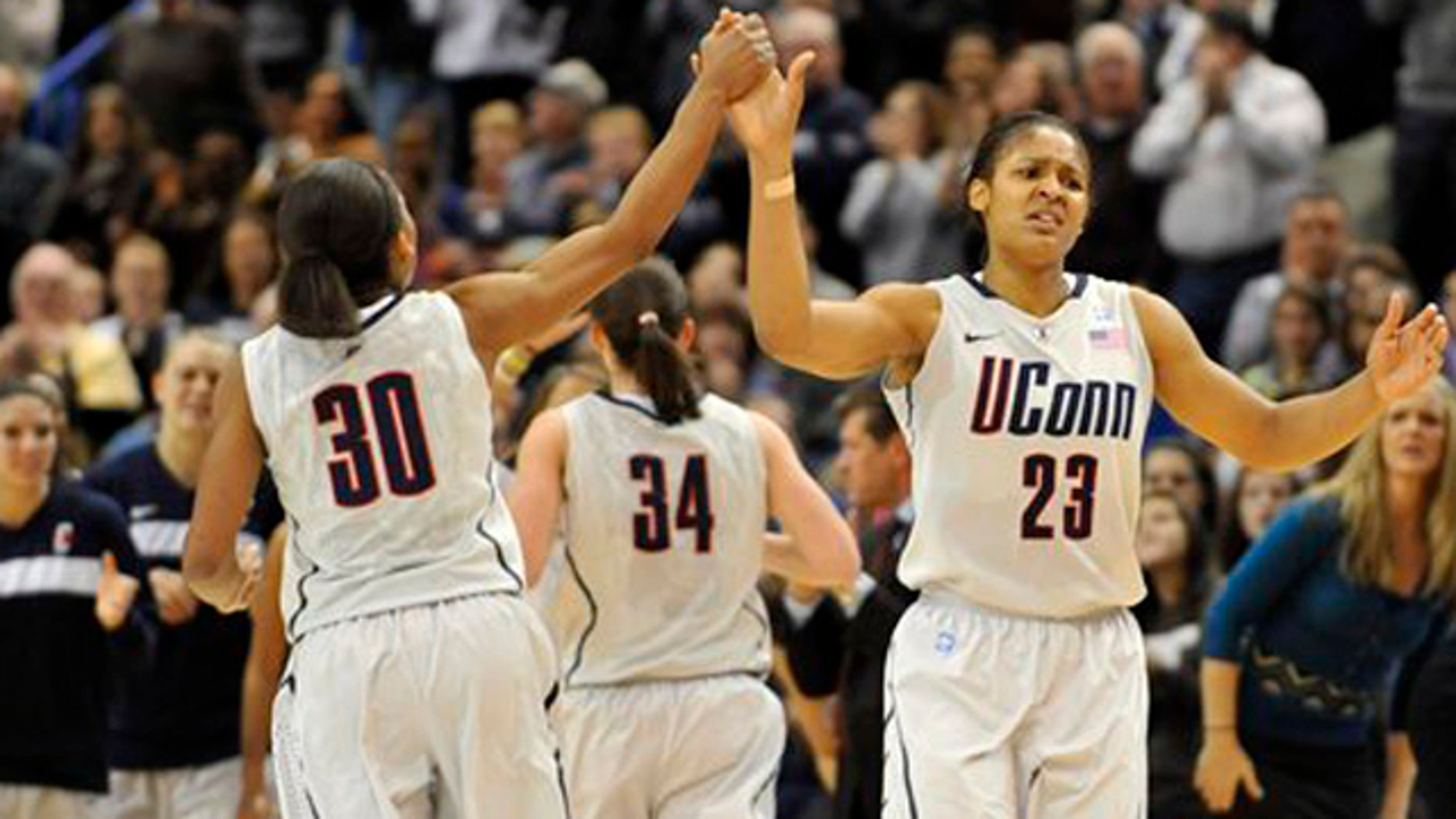 Dec. 5, 2010: Connecticut's Maya Moore, right, high-fives teammate Lorin Dixon after breaking UConn's all time scoring record.