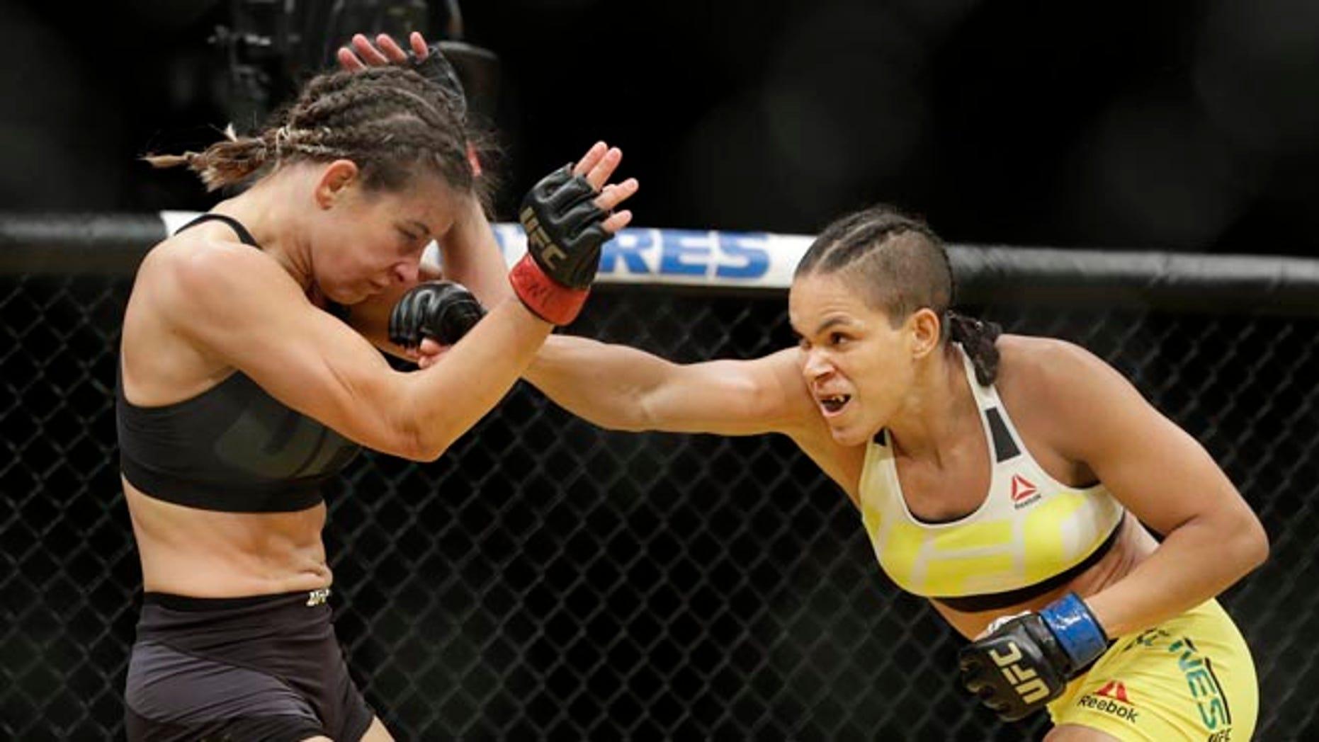 Amanda Nunes, right, hits Miesha Tate during their women's bantamweight championship mixed martial arts bout at UFC 200, Saturday, July 9, 2016, in Las Vegas. (AP Photo/John Locher)
