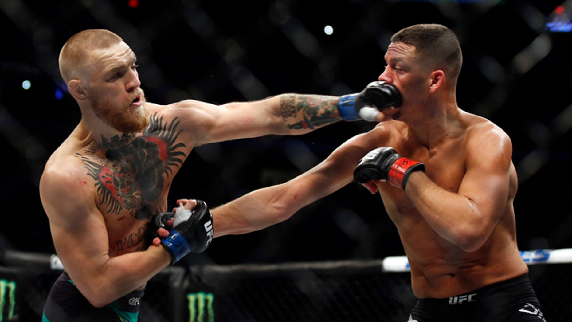 Conor McGregor, left, punches Nate Diaz during their welterweight mixed martial arts bout at UFC 202 on Saturday, Aug. 20, 2016, in Las Vegas. McGregor won by split decision. (AP Photo/Isaac Brekken)
