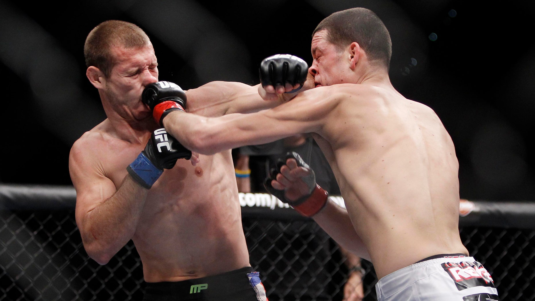 Donald Cerrone, left, trades punches with Nate Diaz during their UFC lightweight mixed martial arts match Friday, Dec. 30, 2011 at The MGM Grand Garden Arena in Las Vegas. Diaz won by unanimous decision. (AP Photo/Eric Jamison)
