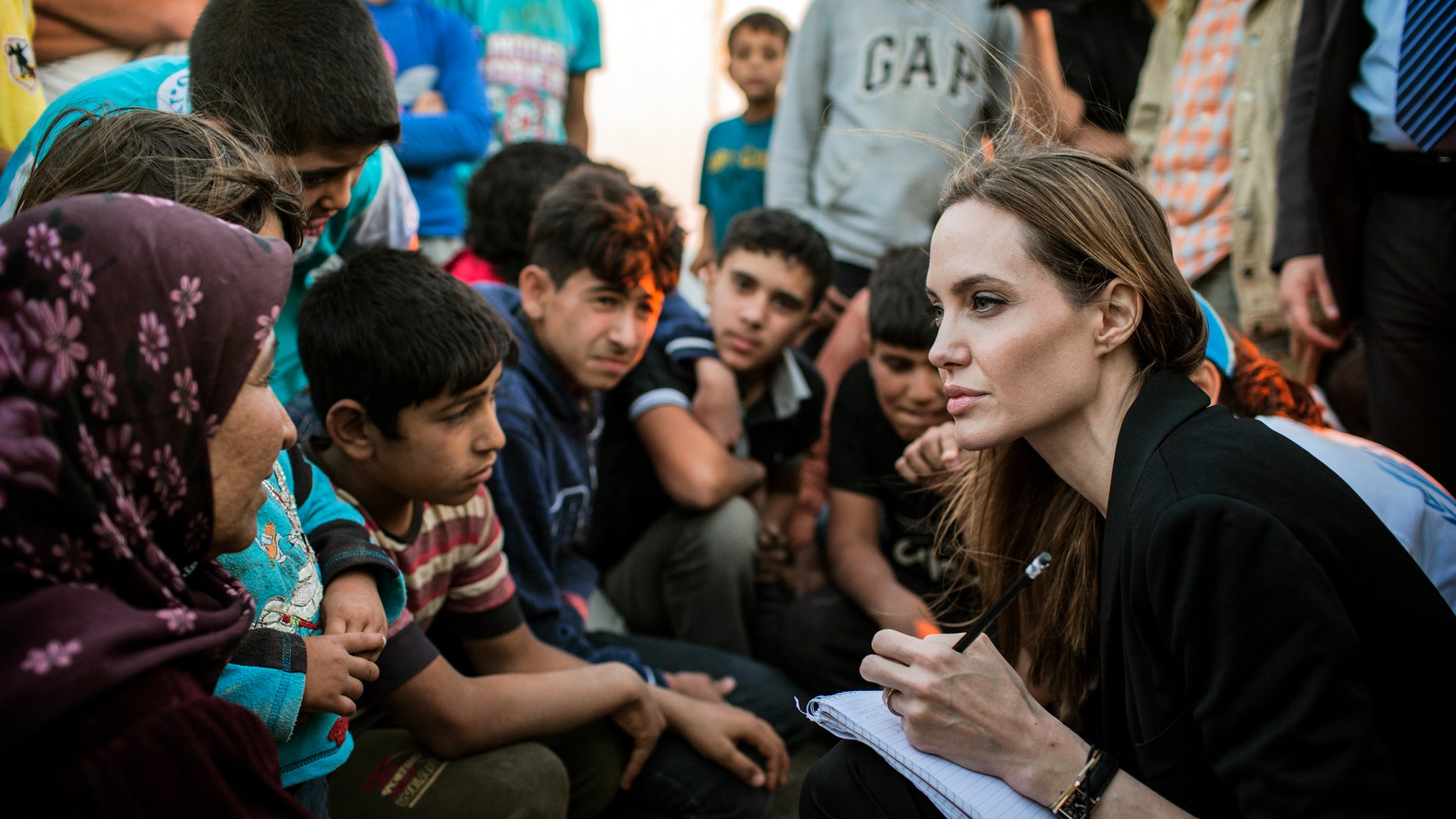 June 18, 2013  - Special envoy Angelina Jolie taking notes as she speaks with Syrian refugees in a Jordanian military camp near the Syria-Jordan border. (photo released by the United Nations High Commissioner for Refugees (UNHCR)