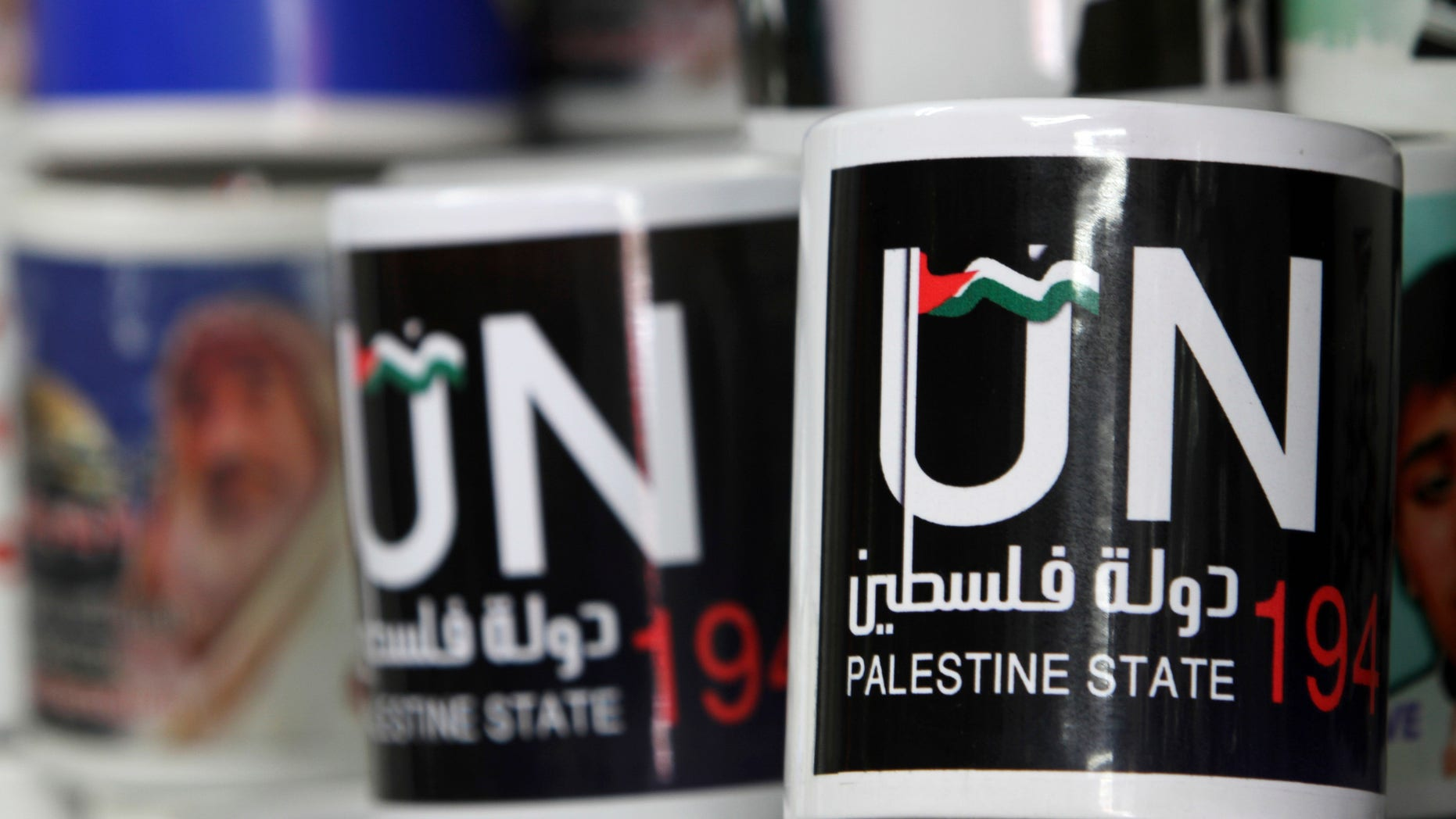 Cups designed as part of the campaign promoting the Palestinians' bid for statehood are displayed in a souvenirs shop in Gaza City, Tuesday, Sept. 13, 2011.