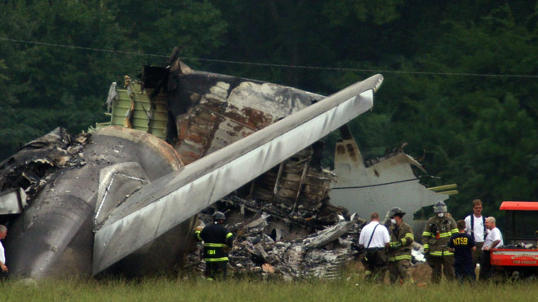 Aug 15, 2013: NTSB investigators work around the tail section of the UPS cargo plane that crashed on approach to the Birmingham-Shuttlesworth International Airport in Birmingham, Ala.