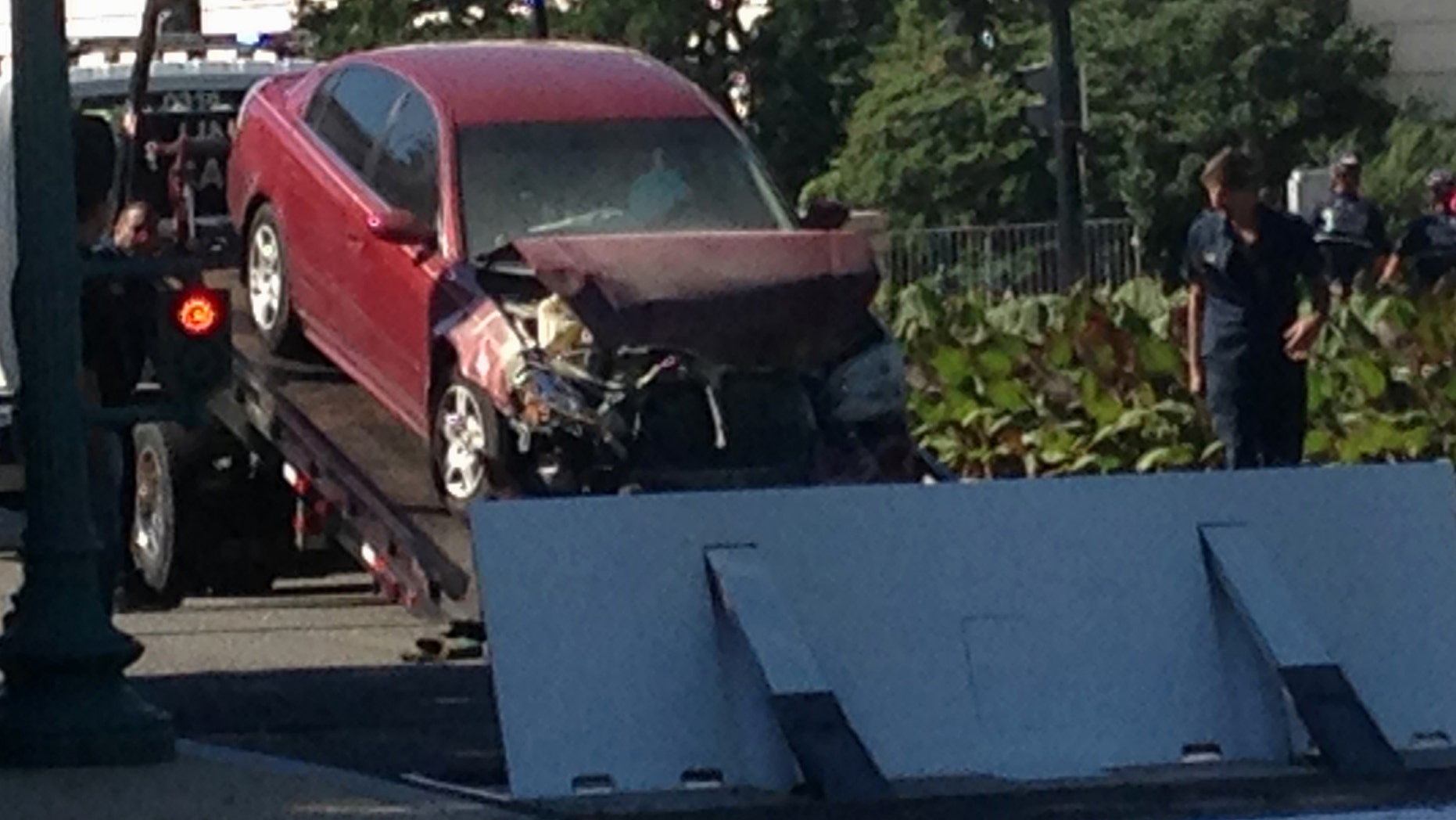 A car is is moved after crashing into a barrier on Capitol Hill in Washington, Friday, July 31, 2015.