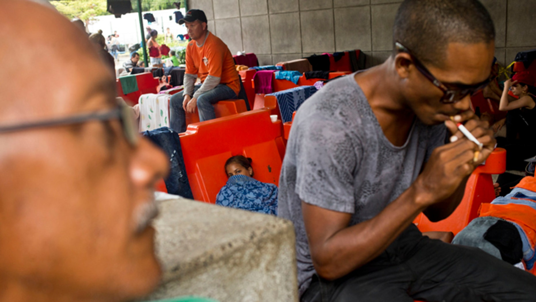 """Cuban migrants sit outside the immigration office in Peñas Blancas, Costa Rica, Tuesday, Nov. 17, 2015. More than 1,000 Cuban migrants heading north to the United States tried to cross the border from Costa Rica into Nicaragua, causing tensions to soar between the neighbors as security forces sought to turn them back. Nicaragua's government responded furiously on Sunday with a statement saying that Costa Rica """"had deliberately and irresponsibly thrown, and continues to throw"""" the Cuban migrants into its territory, violating its national sovereignty. (AP Photo/Esteban Felix)"""