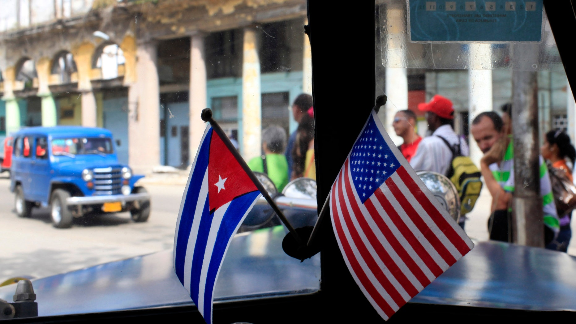 FILE - In this March 22, 2013 file photo, miniature flags representing Cuba and the U.S. are displayed on the dash of an American classic car in Havana, Cuba.  The Obama administration is putting a large dent in the U.S. embargo against Cuba as of Friday, significantly loosening restrictions on American trade and investment. The new rules also open up the communist island to greater American travel and allow U.S. citizens to start bringing home small amounts of Cuban cigars after more than a half-century ban. (AP Photo/Franklin Reyes, File)
