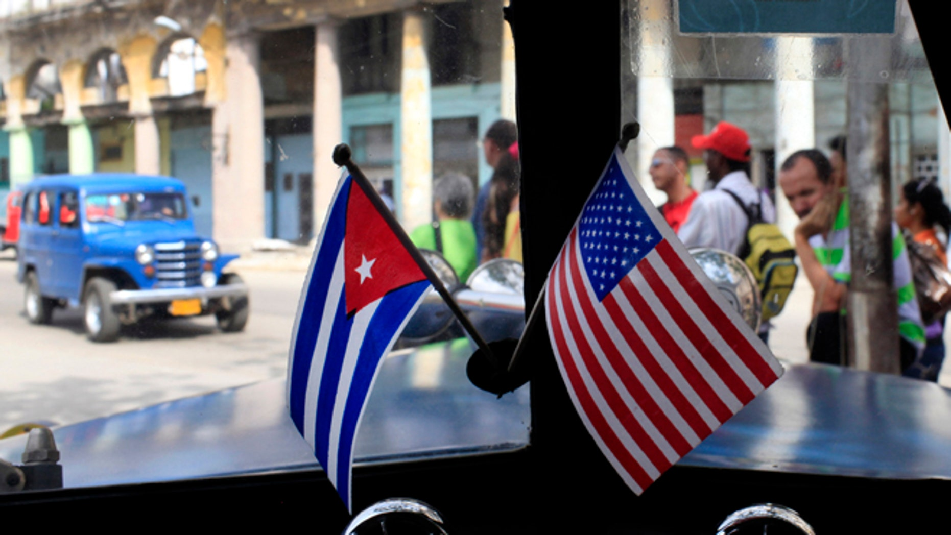 This March 22, 2013 file photo shows miniature flags representing Cuba and the U.S. displayed on the dash of an American classic car in Havana, Cuba.