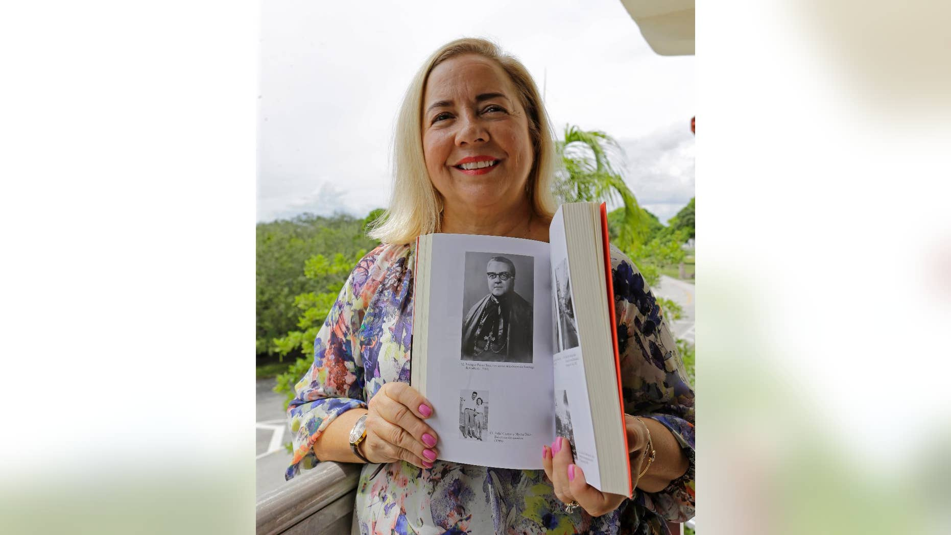 In this Sept. 10, 2015 photo, Frances Serantes Gomez poses with a photo of her great uncle, Archbishop Enrique Perez Serantes, at her home in Coral Gables, Florida. Serantes Gomez's great uncle is the former archbishop of Santiago, Cuba who saved Fidel Castro's life. After Castro seized power, Serantes' support turned to opposition and the prelate's family fled. Frances is among several hundred Cuban-Americans expected to make a pilgrimage to Cuba for Pope Francis' visit, and among thousands who are trying to finally put five decades of bitterness behind them. (AP Photo/Alan Diaz)
