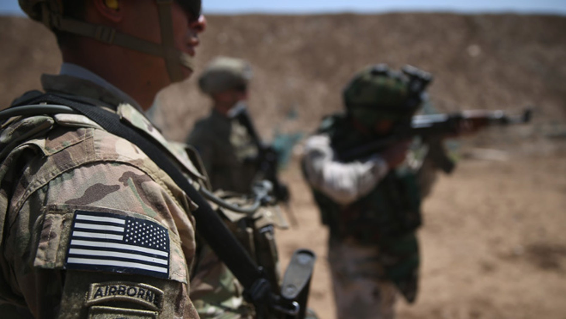 TAJI, IRAQ - APRIL 12:  U.S. Army trainers watch as an Iraqi recruit fires at a military base on April 12, 2015 in Taji, Iraq. U.S. forces, currently operating in 5 large bases throught the country, are training thousands of Iraqi Army combat troops, trying to rebuild a force they had origninally trained before the U.S. withdrawal from Iraq in 2010. Members of the U.S. Army's 5-73 CAV, 3BCT, 82nd Airborne Division are teaching members of the newly-formed 15th Division of the Iraqi Army, as the Iraqi government launches offensives to try to recover territory lost to ISIS last year.  (Photo by John Moore/Getty Images)