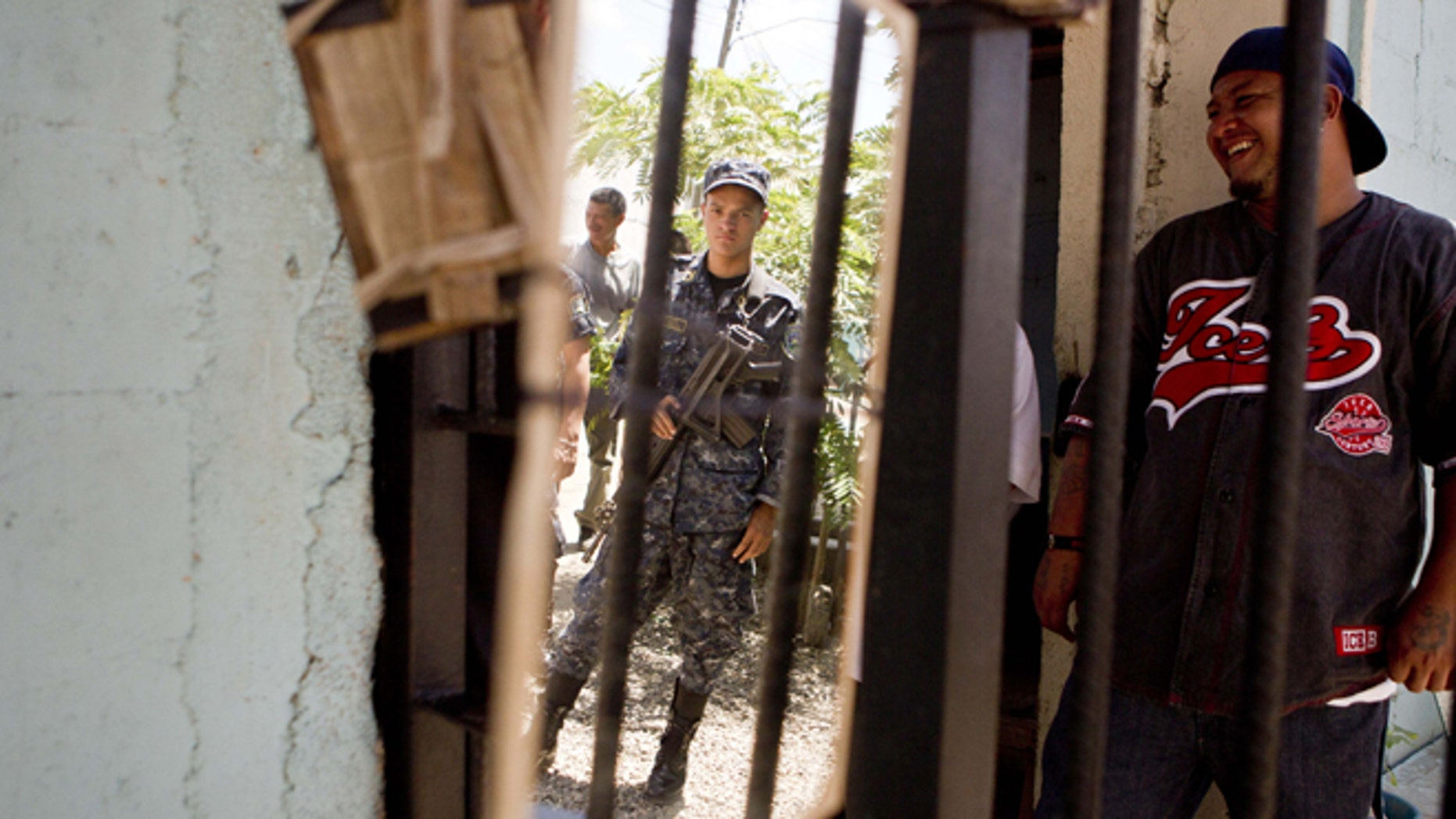 A National Police officer is reflected in a mirror hanging inside the area of gang members from the Mara Salvatrucha, MS, inside the San Pedro Sula prison in Honduras, Tuesday, May 28, 2013. Honduras' largest and most dangerous street gangs have declared a truce, offering the government peace in exchange for rehabilitation and jobs. A Mara Salvatrucha gang spokesman says the gang and its rival, 18th Street, will commit to zero violence and zero crime in the streets as first step show of good faith. (AP Photo/Esteban Felix)