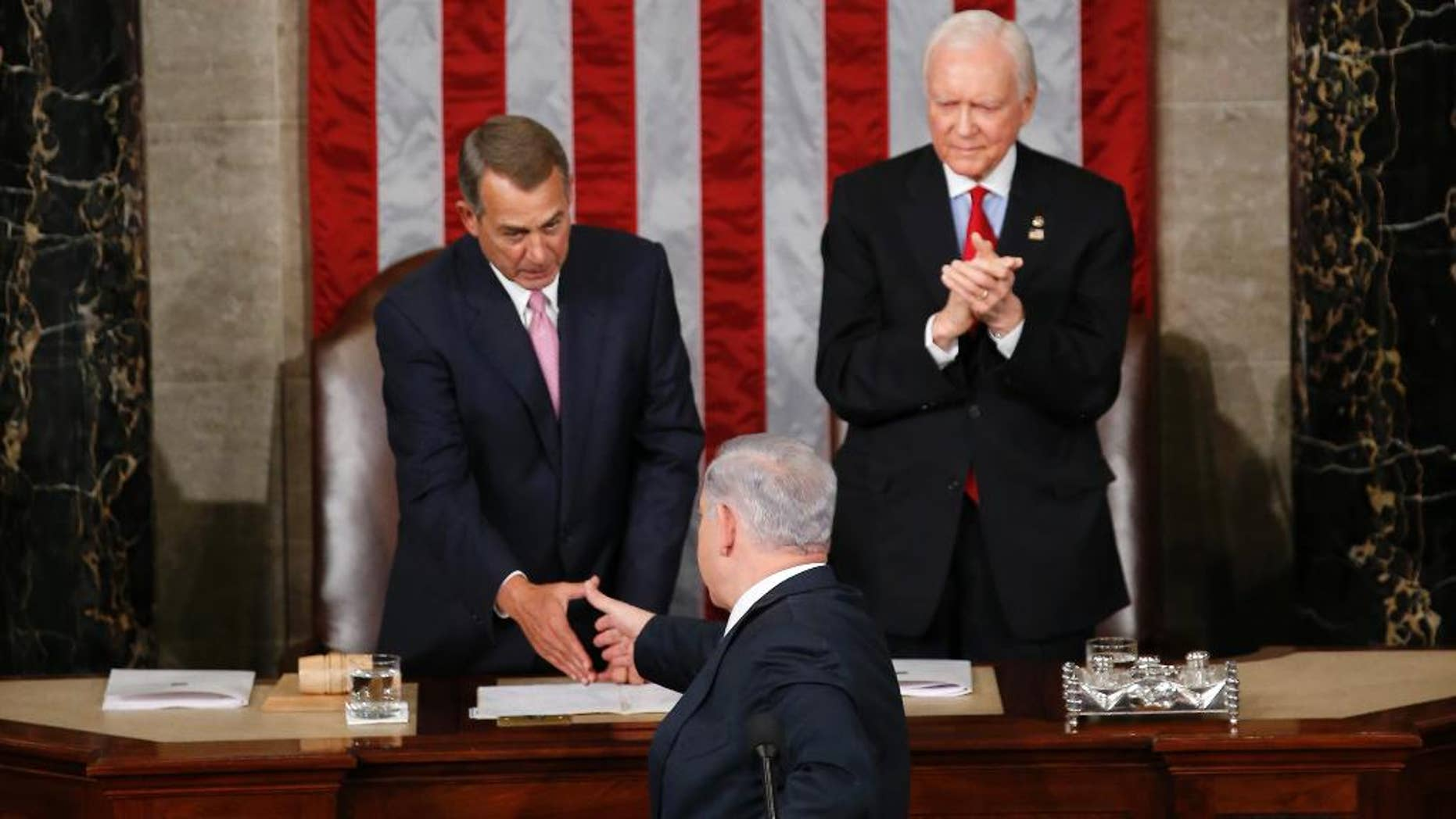 """Israeli Prime Minister Benjamin Netanyahu turns and shake hands with House Speaker John Boehner of Ohio hand after addressing a joint meeting of Congress on Capitol Hill in Washington, Tuesday, March 3, 2015. In a speech that stirred political intrigue in two countries, Netanyahu told Congress that negotiations underway between Iran and the U.S. would """"all but guarantee"""" that Tehran will get nuclear weapons, a step that the world must avoid at all costs. Sen. Orrin Hatch, R-Utah applauds at right.  (AP Photo/Andrew Harnik)"""