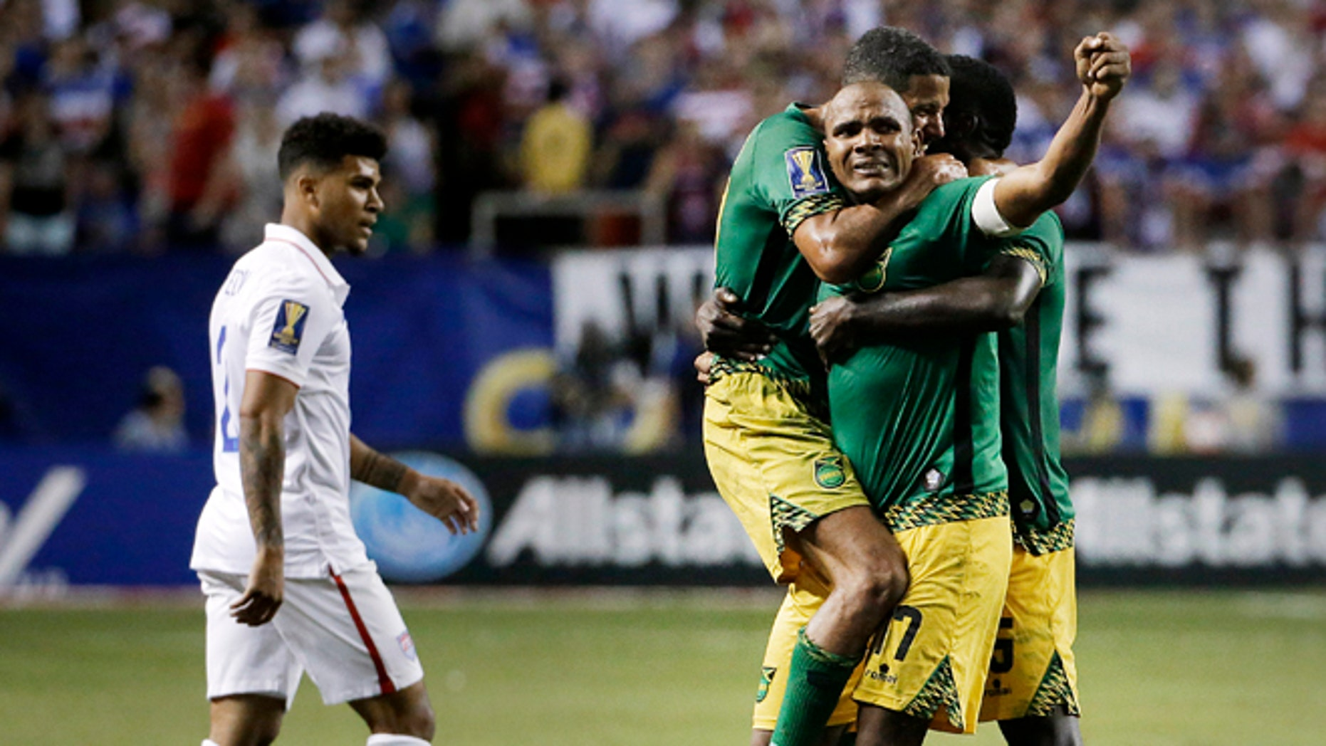 Jamaicas Rudolph Austin, facing camera, celebrates with teammates Joel McAnuff, left, and Je-Vaughn Watson, right, as United States DeAndre Yedlin walks off the pitch after Jamaica defeated the United States 2-1 in a CONCACAF Gold Cup soccer semifinal Wednesday, July 22, 2015, in Atlanta. (AP Photo/David Goldman)