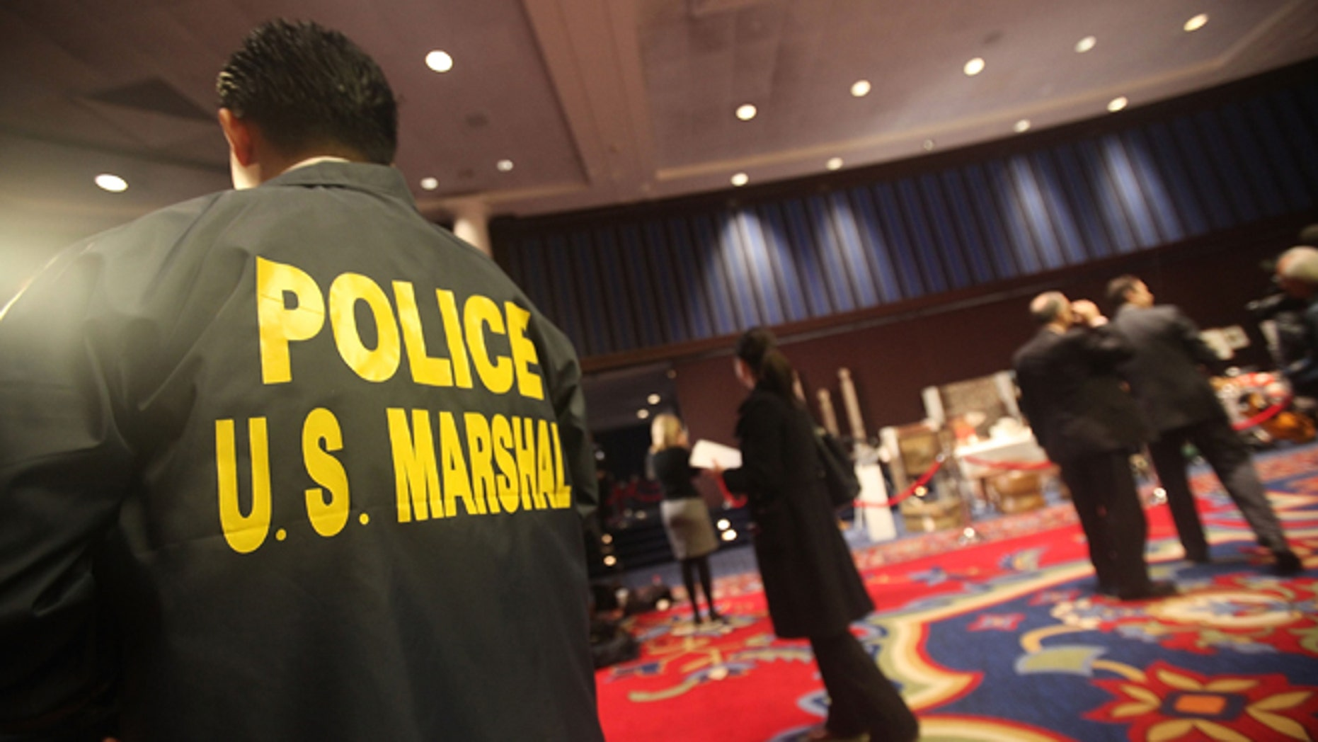 NEW YORK - NOVEMBER 13:  A U.S. Marshal looks on during a press preview of a U.S. Marshals Service auction of personal property seized from Bernard and Ruth Madoff November 13, 2009 in New York City. The property includes jewelry, furs, artwork and other items forfeited in connection with the criminal prosecution of Bernard Madoff's Ponzi scheme.  (Photo by Mario Tama/Getty Images)