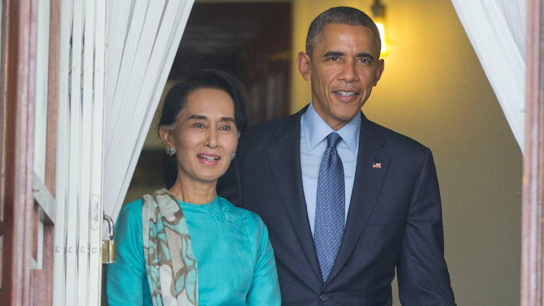 FILE - In this Nov. 14, 2014 file photo, President Barack Obama walks with Myanmar's opposition leader Aung San Suu Kyi for their joint news conference at her home in Yangon, Myanmar. Human rights advocates and some lawmakers say the United States is sending the wrong signal by opening the door for broader cooperation with Myanmar's widely criticized military just weeks after President Barack Obama assured opposition leader Aung San Suu Kyi that closer ties weren't going to happen soon.  (AP Photo/Pablo Martinez Monsivais, File)