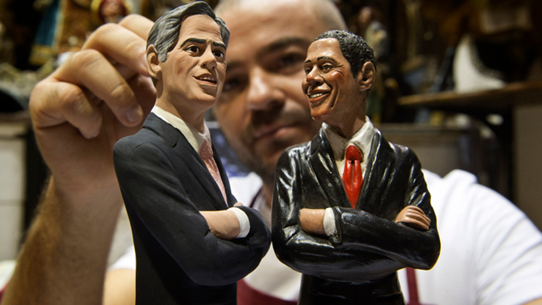 Italian Nativity scenes designer Genny Di Virgilio puts the final touches on two statuettes depicting President Barack Obama, right, and Republican rival Mitt Romney in his shop in Naples, Italy, Monday, Oct. 22, 2012, hours ahead of their third and final presidential debate in Boca Raton, Florida. (AP Photo/Salvatore Laporta)