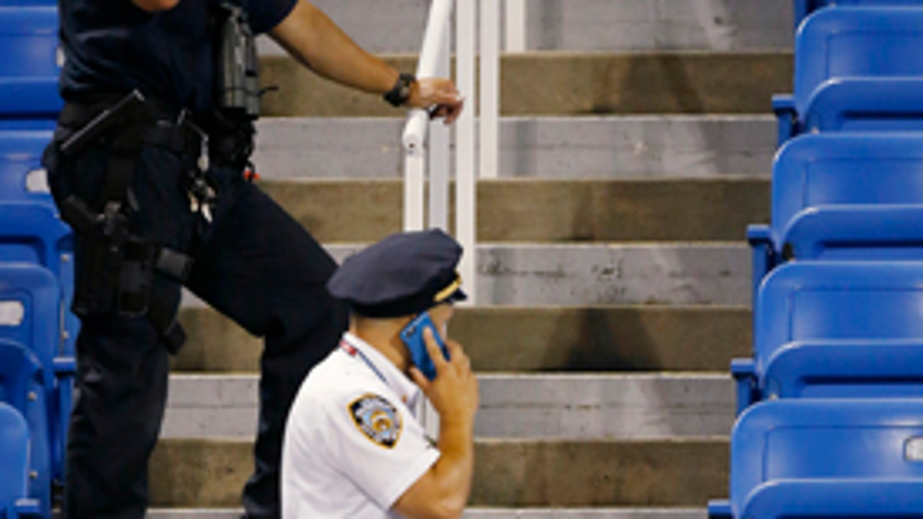 Sept. 3, 2015: Police officers investigate the southwest corner of Louis Armstrong Stadium after a drone flew over the court, buzzing the players during a match between Flavia Pennetta and Monica Niculescu during the second round of the U.S. Open tennis tournament in New York. The drone crashed into the seats and can be seen to the right of the police officer on his phone. (AP Photo/Kathy Willens)
