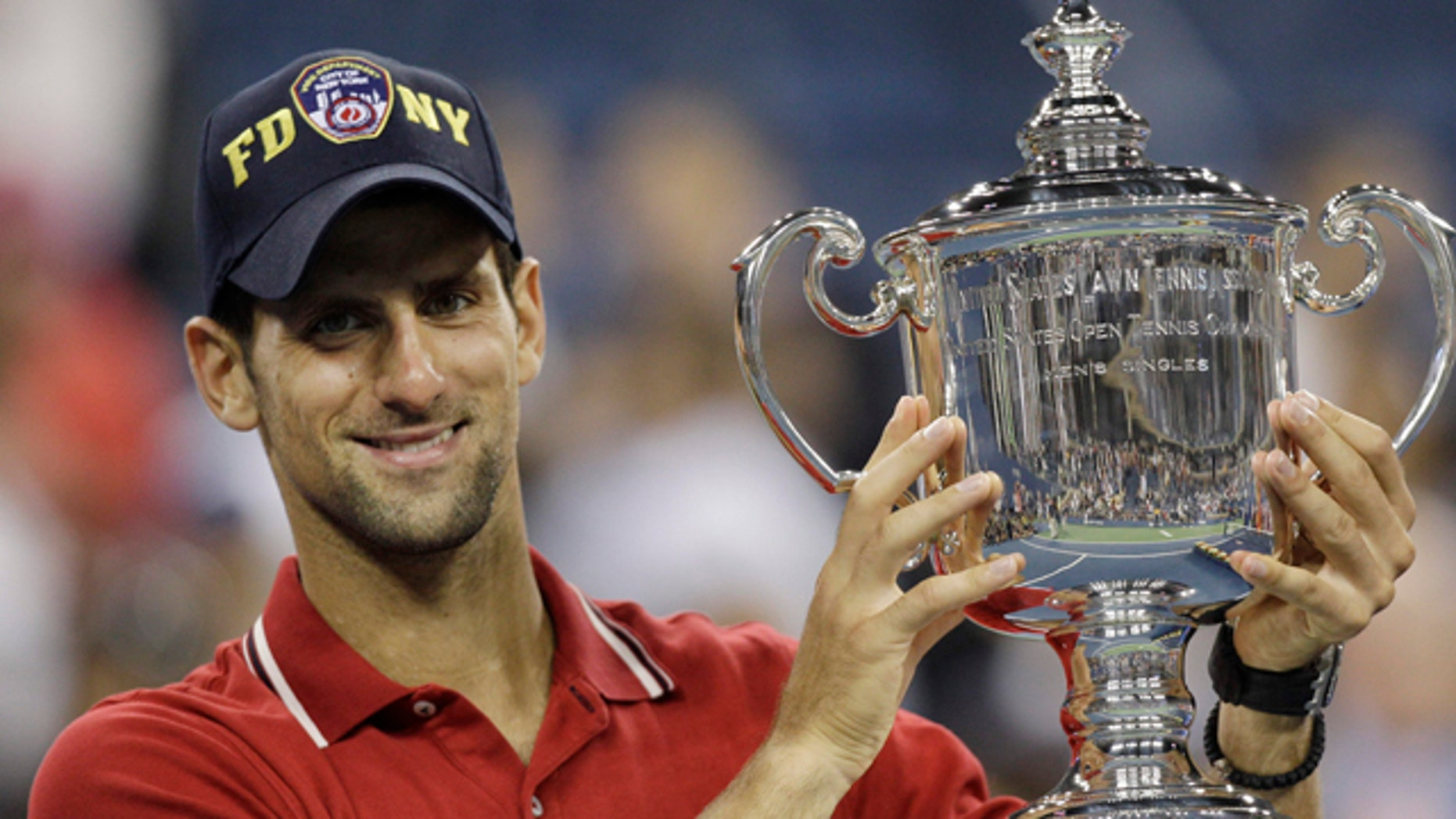 Novak Djokovic of Serbia poses with the trophy after winning the men's championship match against Rafael Nadal of Spain at the U.S. Open tennis tournament in New York, Monday, Sept. 12, 2011. (AP Photo/Matt Slocum)