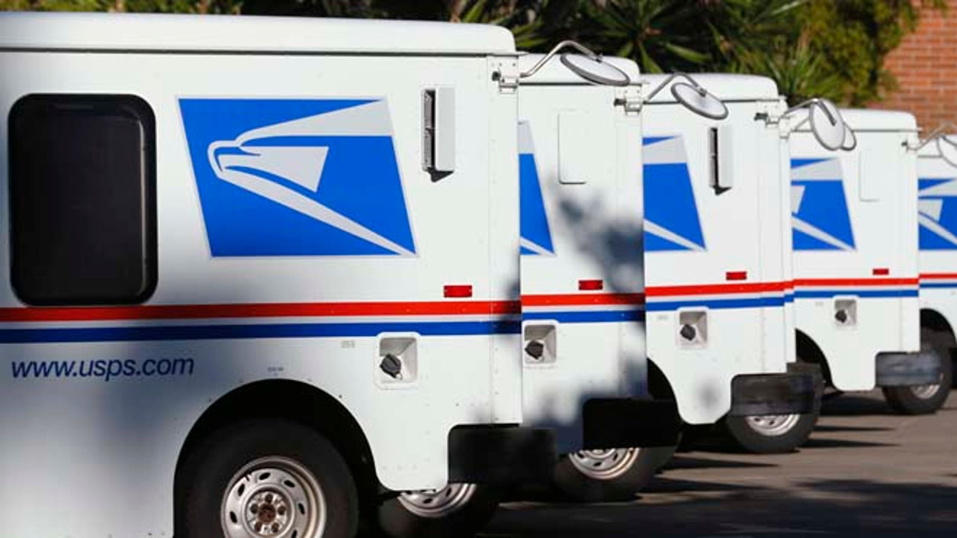 In this Nov. 13, 2013 file photo U.S. postal service trucks sit parked at the post office in Del Mar, California.