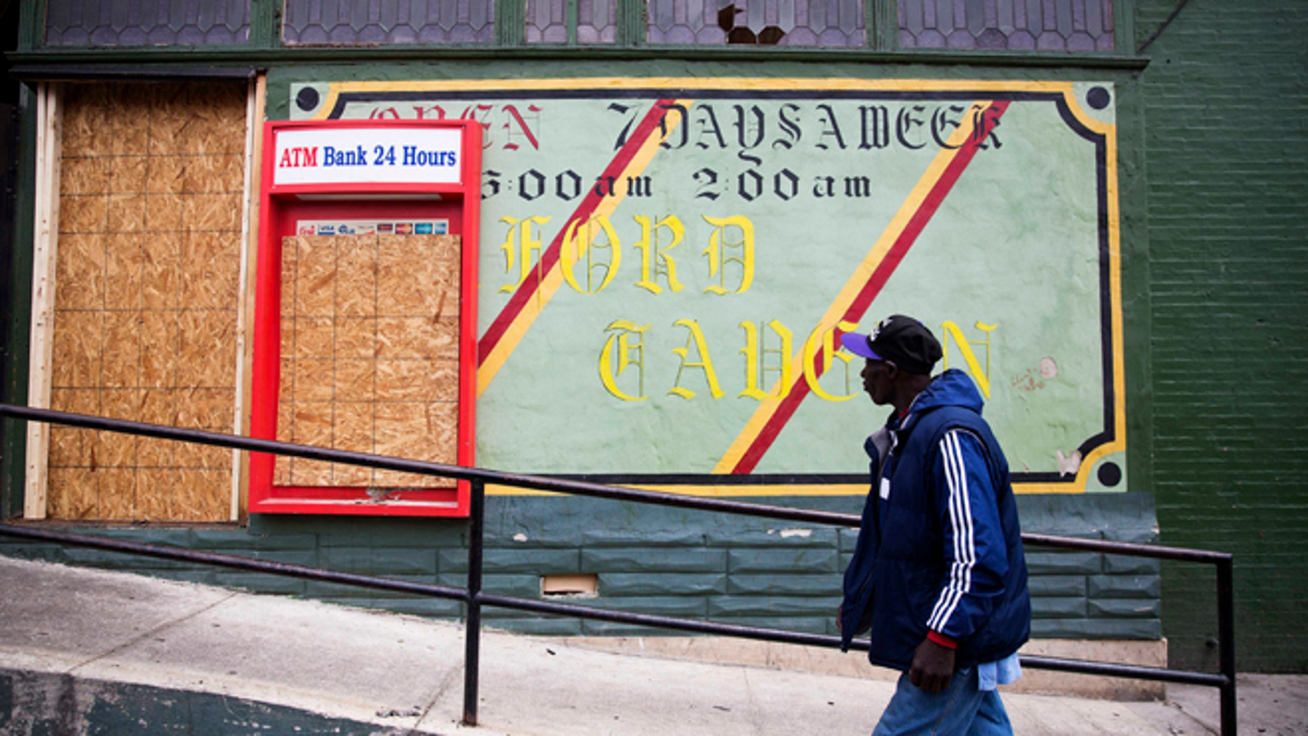 FILE - In this April 30, 2015 file photo, a man walks past the damaged Oxford Tavern in Baltimore. In a presidential campaign where candidates are jockeying to be champions of the middle class and courting donations from the wealthy, the poor are inching their way into the debate. Tensions in Baltimore, Ferguson, Missouri, and elsewhere have sparked examinations of the relationship between poor communities and the police, as well as the systemic problems that have trapped many of the 45 million Americans living in poverty. But addressing the economic, education, and security issues that have plagued underprivileged neighborhoods for decades remains a politically elusive challenge. (AP Photo/David Goldman, File)