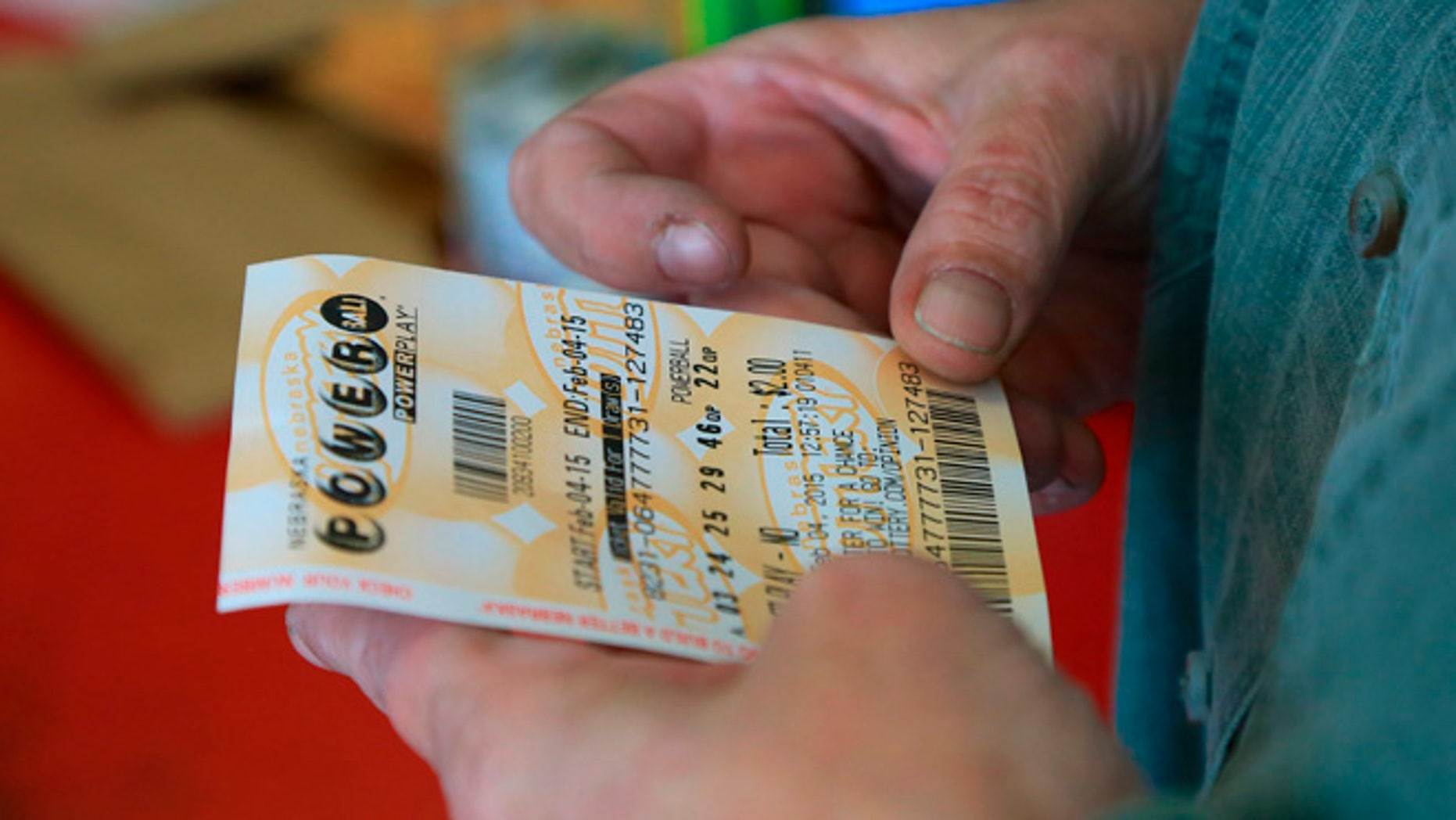 Feb. 4, 2015: A customer inspects the Powerball ticket she purchased at a U-Stop store in Lincoln, Neb.