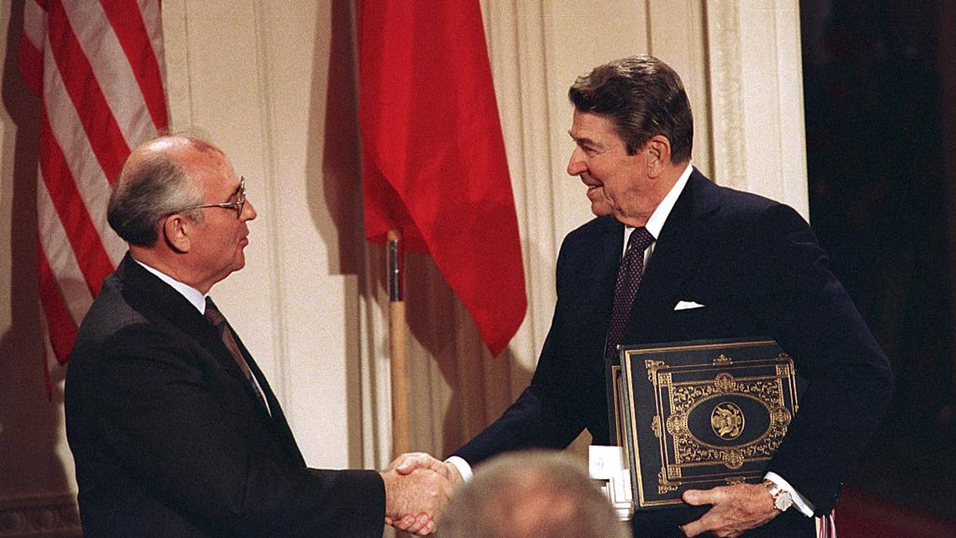 """FILE - Int this Dec. 8, 1987, file photo, U.S. President Ronald Reagan, right, shakes hands with Soviet leader Mikhail Gorbachev after the two leaders signed the Intermediate Range Nuclear Forces Treaty to eliminate intermediate-range missiles during a ceremony in the White House East Room in Washington. In an escalation of tensions, the Obama administration accused Russia on July 28, 2014, of conducting tests in violation of a 1987 nuclear missile treaty, calling the breach """"a very serious matter"""" and going public with allegations that have simmered for some time. The treaty confrontation comes at a highly strained time between President Barack Obama and Russian President Vladimir Putin over Russia's intervention in Ukraine and Russia's grant of asylum to National Security Agency leaker Edward Snowden.(AP Photo/Bob Daugherty, File)"""