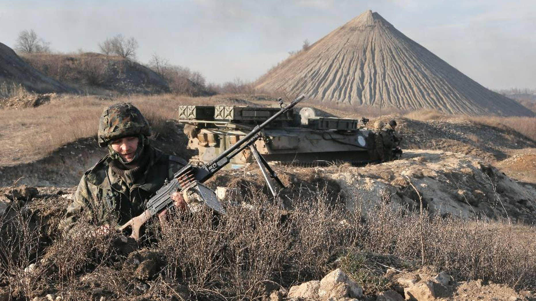 """FILE - In this March 11, 2015, file photo, a Ukrainian serviceman takes position at the front line outside Kurahovo, in the Donetsk region of Ukraine. The United States now sees the Ukrainian rebels as a Russian force. American officials briefed on intelligence from the region say Russia has significantly deepened its command and control of the militants in eastern Ukraine in recent months, leading the U.S. to quietly introduce a new term: """"combined Russian-separatist forces."""" (AP Photo/Efrem Lukatsky, File)"""