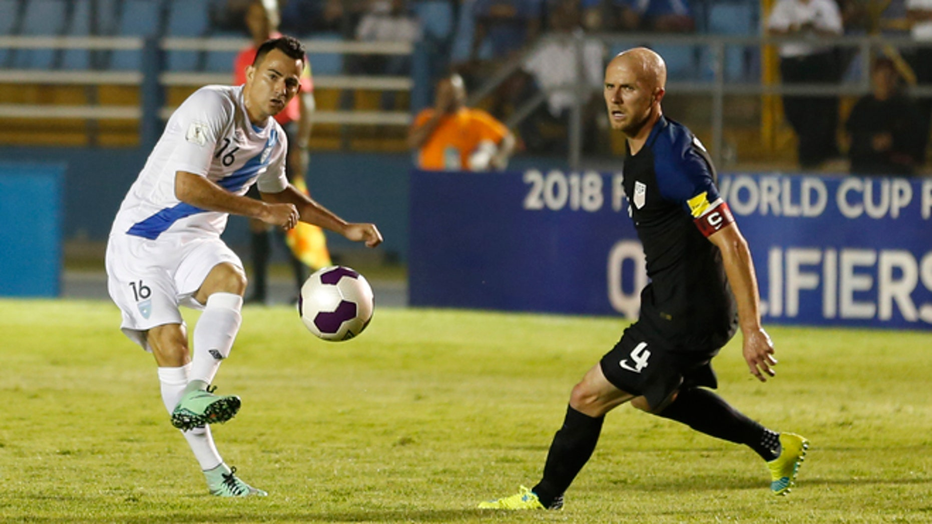 Guatemala's Marco Papa, left, kicks the ball as United States' Michael Bradley looks on during a 2018 Russia World Cup qualifying soccer match at Mateo Flores Stadium in Guatemala City, Friday, March 25, 2016. Guatemala won 2-0. (AP Photo/ Moises Castillo)