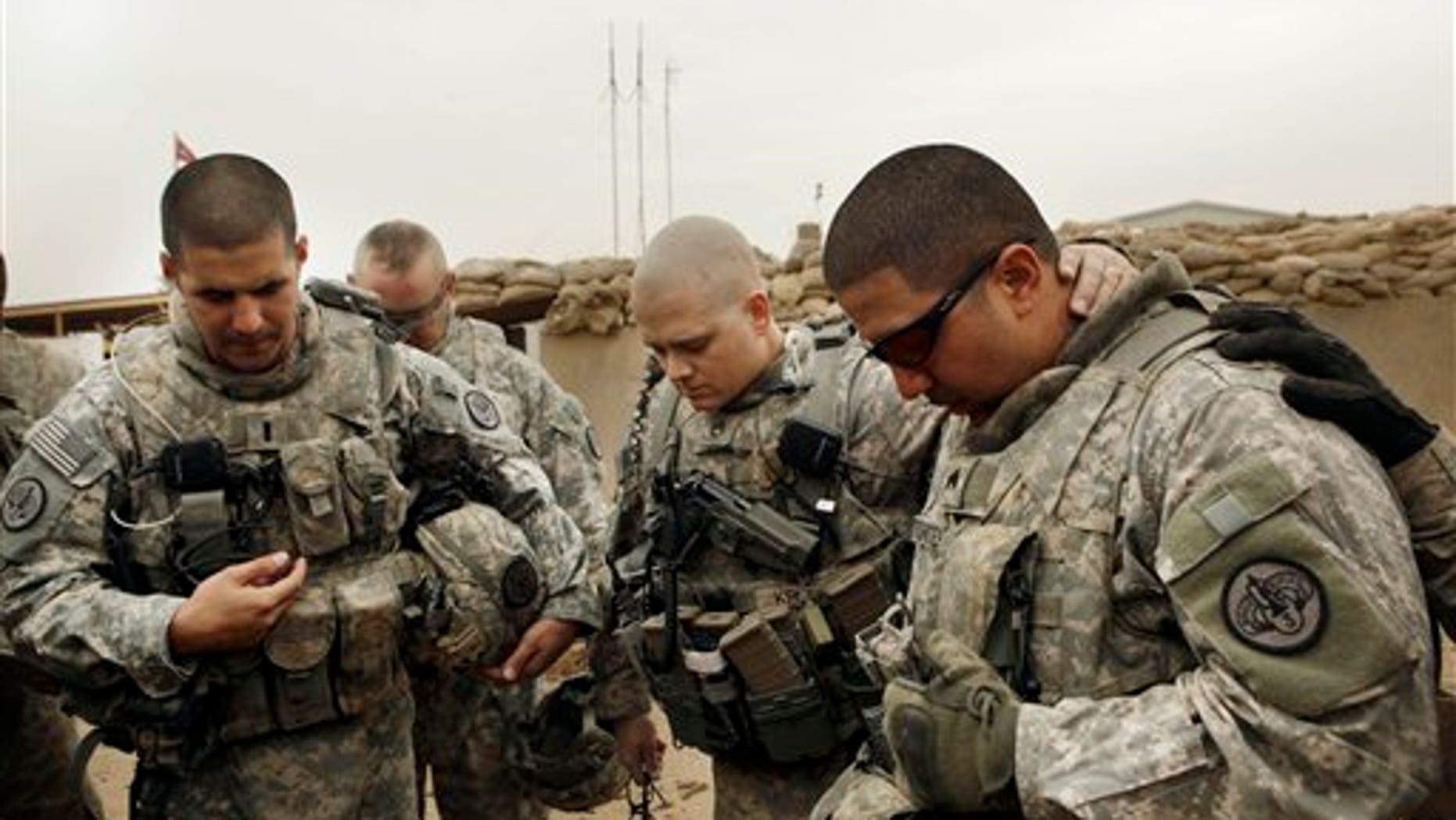 Jan. 2011: U.S. Army Lt. Daniel McCord, left, Staff Sgt. Marc Krugh, center and Sgt. Christopher Torrentes, right, from the 3rd Armored Cavalry Regiment pray before heading out on a patrol at Contingency Operating Site Kalsu, south of Baghdad, Iraq.