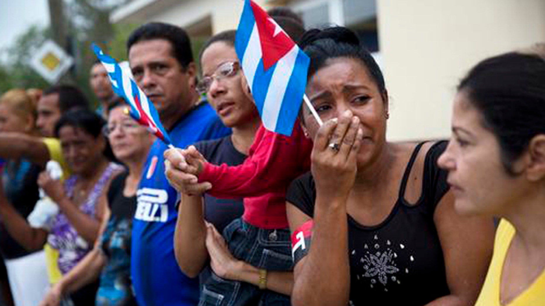 A woman weeps after watching the ashes of Cuban leader Fidel Castro along the main road in Baire, eastern Cuba, Saturday, Dec. 3, 2016. The convoy is on the last stage of a four-day journey across Cuba through small towns and cities where his rebel army fought its way to power nearly 60 years ago, to the eastern city of Santiago, where his remains will be interred on Sunday. (AP Photo/Rodrigo Abd)