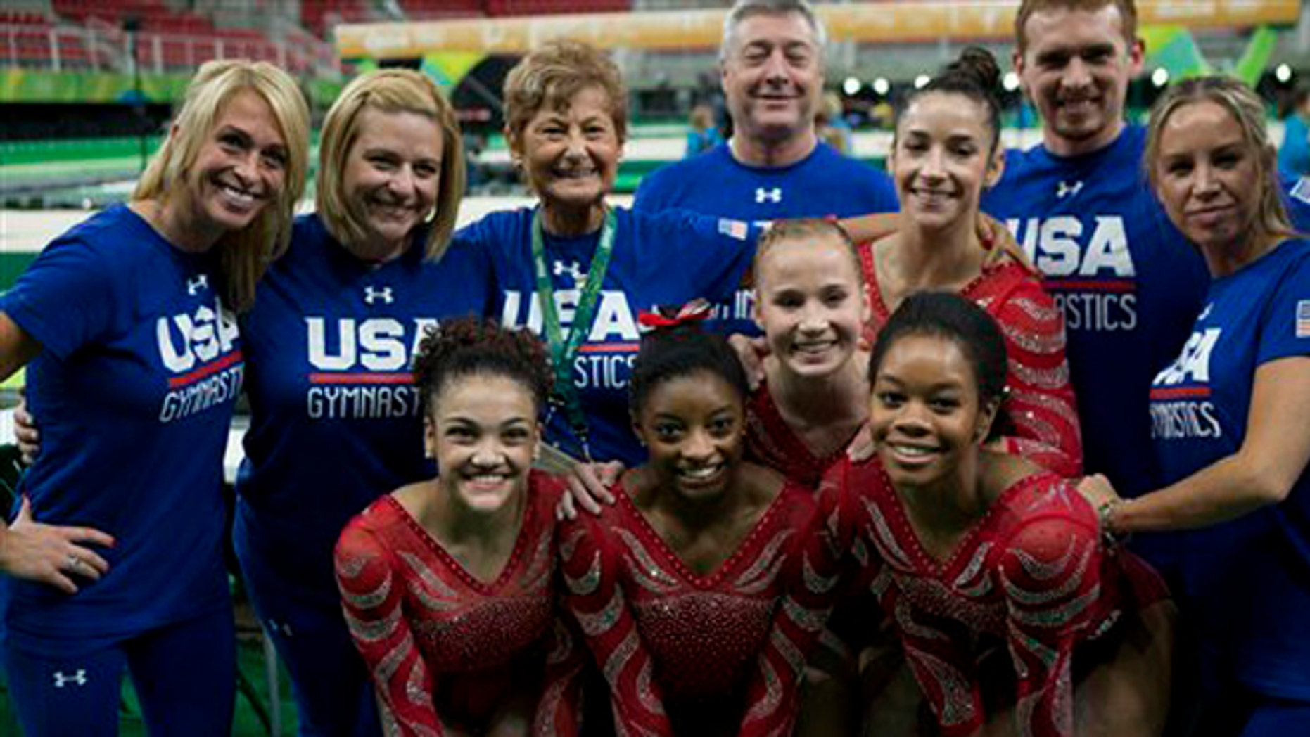 The United States women's gymnastic team poses for a picture with their coaching staff after finishing podium training ahead of the 2016 Summer Olympics in Rio de Janeiro, Brazil, Thursday, Aug. 4, 2016. Front row, from left, are gymnasts Lauren Hernandez, Simone Biles, and Gabby Douglas. Behind them are Madison Kocian, left, and Alexandra Raisman. Head coach Martha Karolyi is back row, third from left.(AP Photo/Rebecca Blackwell)