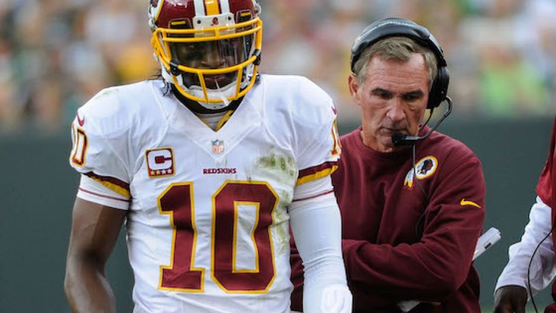 Sep 15, 2013; Green Bay, WI, USA; Washington Redskins quarterback Robert Griffin III (10) and head coach Mike Shanahan walk on the sidelines during the game against the Green Bay Packers in the third quarter at Lambeau Field. Mandatory Credit: Benny Sieu-USA TODAY Sports