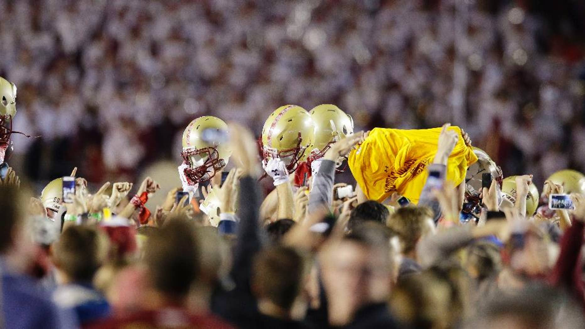 Celebrating members of the Boston College team, holding their helmets above their heads, are surrounded by celebrating fans after they defeated Southern California in their NCAA college football game Saturday, Sept. 13, 2014 in Boston. Boston College defeated USC 37-3. (AP Photo/Stephan Savoia)