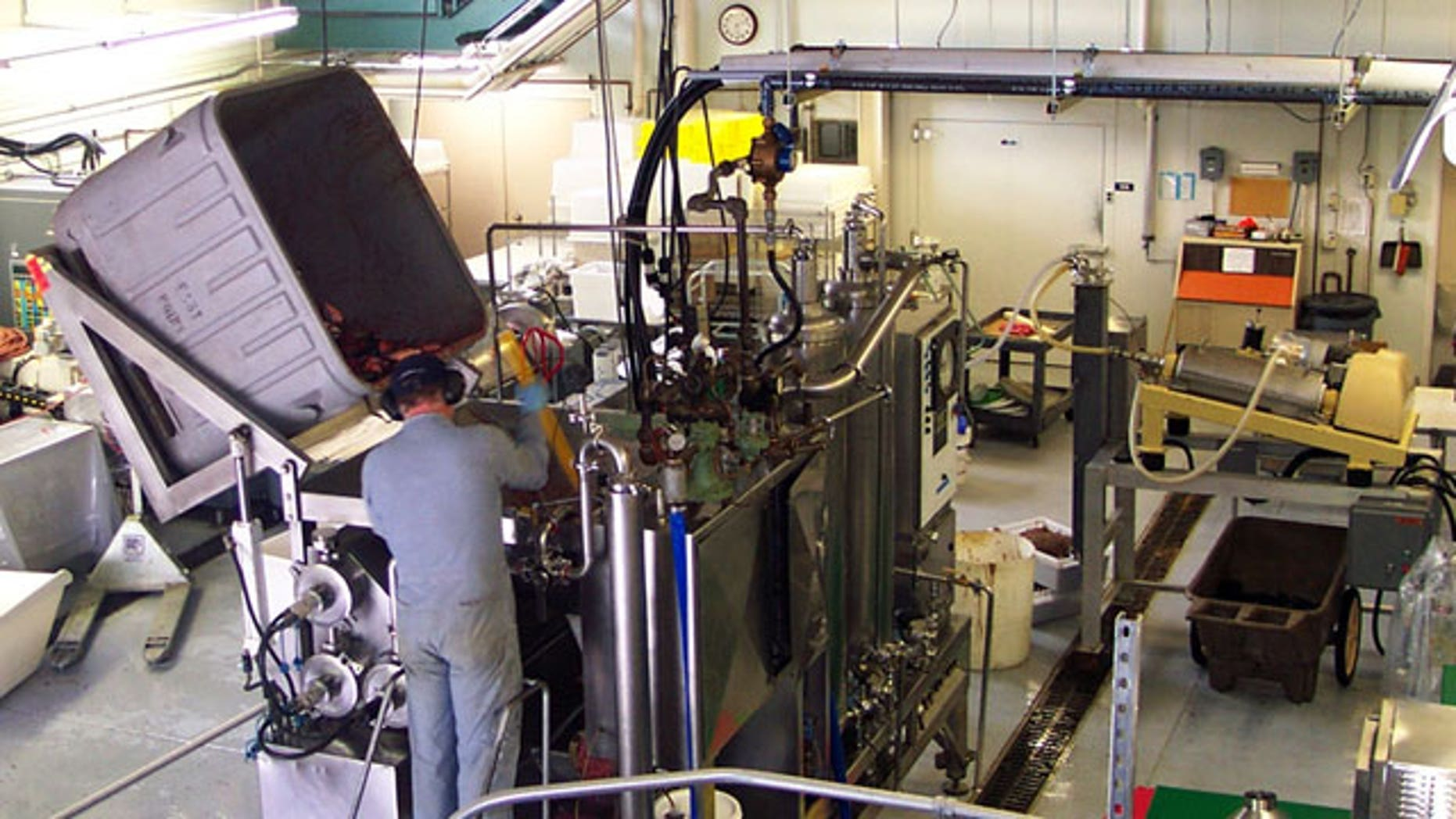 FILE: A technician dumps seafood byproducts into a hydrolysis machine at the Fishery Industrial Technology Center in Kodiak, Alaska.