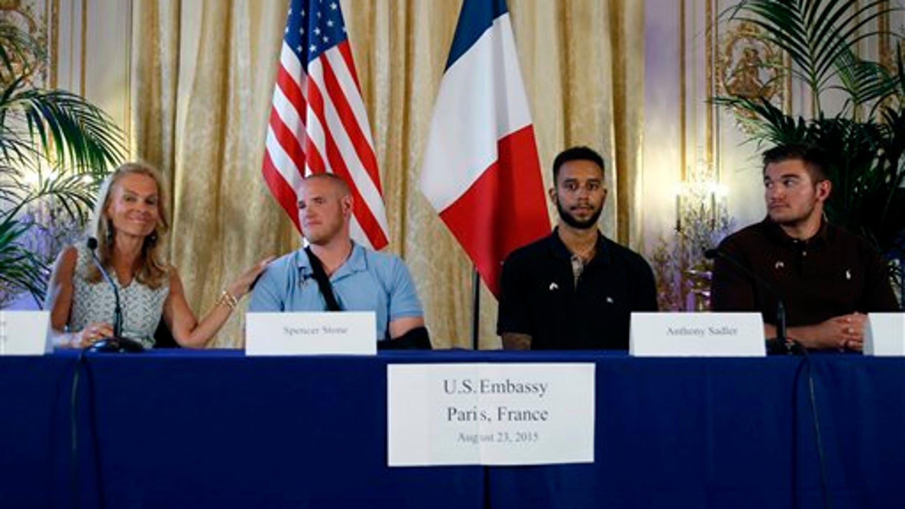 From left, U.S. Ambassador to France Jane D. Hartley, U.S. Airman Spencer Stone, Anthony Sadler, and National Guardsman Alek Skarlatos at press conference in Paris, France, Sunday, Aug. 23, 2015.. (AP Photo/Francois Mori)