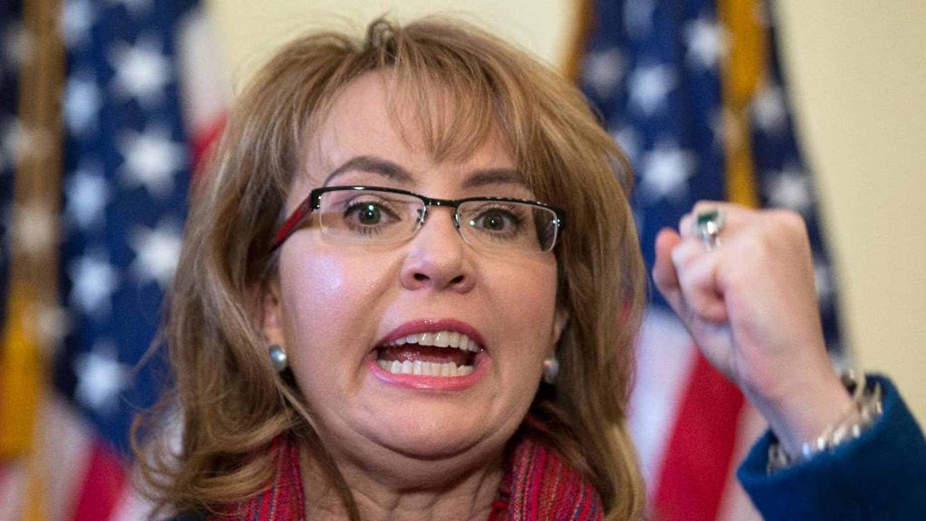 """FILE - In this March 4, 2015, file photo, former U.S. Rep. Gabrielle """"Gabby"""" Giffords of Arizona gestures as she speaks on Capitol Hill in Washington. Giffords is being recognized with a Navy ship named in her honor at a shipyard in Mobile, Alabama. Giffords is set to attend the Saturday, June 13, 2015,  christening of the USS Gabrielle Giffords.  (AP Photo/Carolyn Kaster, File)"""