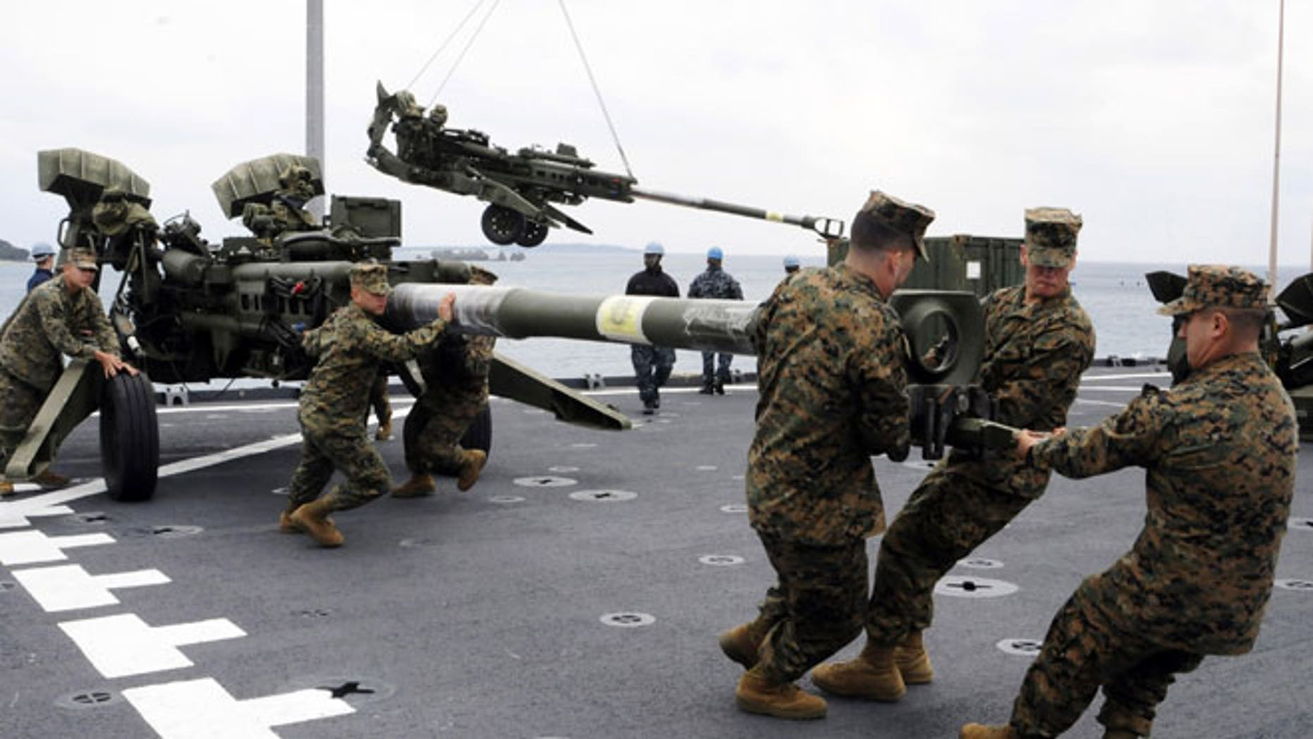 In this Feb. 2, 2012 file photo released by U.S. Navy, U.S. Marines assigned to the 31st Marine Expeditionary Unit haul a 155 mm Howitzer onto the flight deck of the forward-deployed amphibious dock landing ship USS Germantown in Okinawa, Japan, when the ship pulled into Okinawa to embark the Marines in preparation of exercise Cobra Gold 2012.
