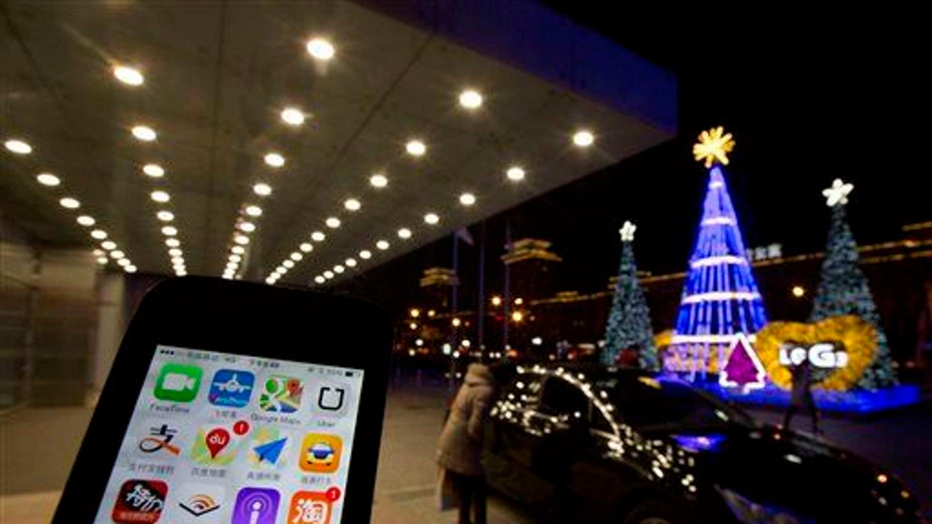The Uber app is displayed on a phone outside an office building in Beijing, Jan. 9, 2015.