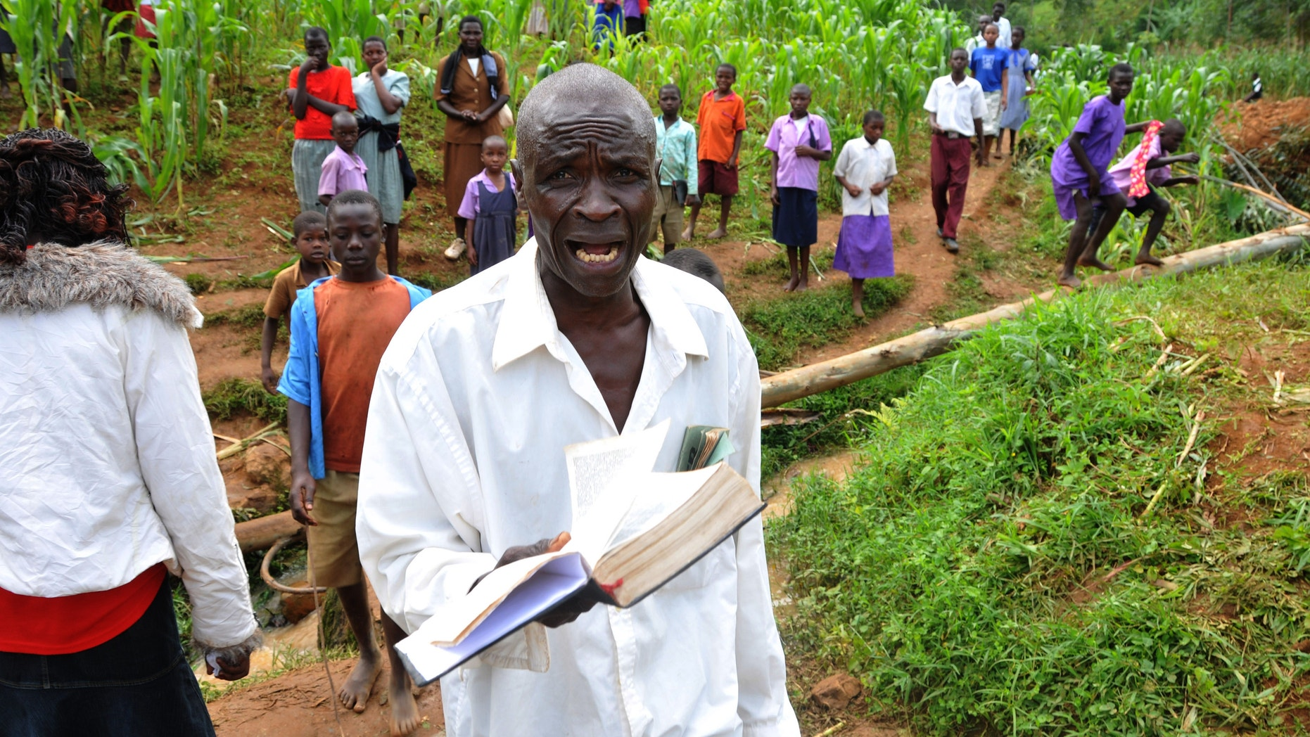 June 26, 2012: A man holding a bible cries out for God's mercy at the landslide in Bududa, about 250km east of Uganda capital Kampala.