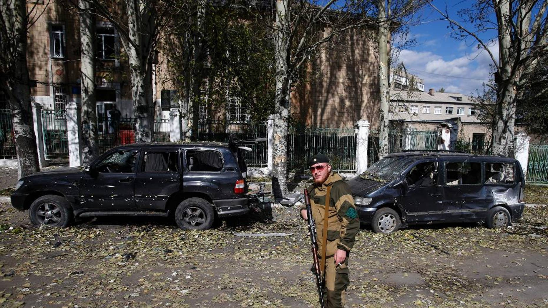 Oct. 1, 2014: A pro-Russian rebel guards a damaged school after shelling in the town of Donetsk, eastern Ukraine. Rebels in eastern Ukraine appear to be successfully closing in on the government-held airport of Donetsk, a strategic victory for the pro-Russian separatists that further undermines a shaky cease-fire in the region.