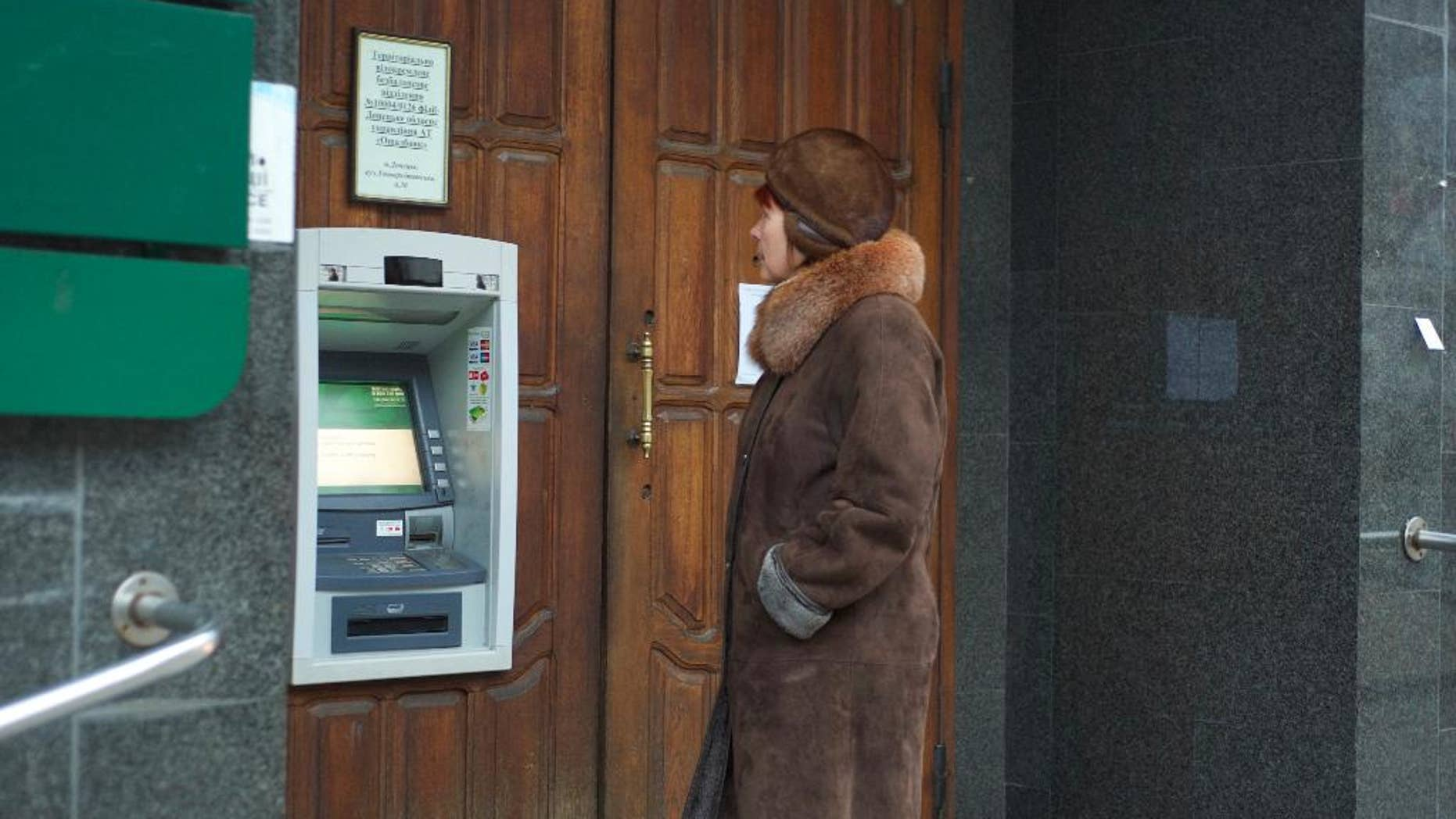 A woman stands at an ATM that doesn't work outside a Ukrainian bank in Donetsk, eastern Ukraine, Tuesday, Nov. 25, 2014. Money is running short in the rebel heartland since the government announced this month that it will suspend banking services as it piles on the pressure. Almost all ATMs have stopped working and the remainder are expected to stop operating over the next two weeks. (AP Photo/Balint Szlanko)