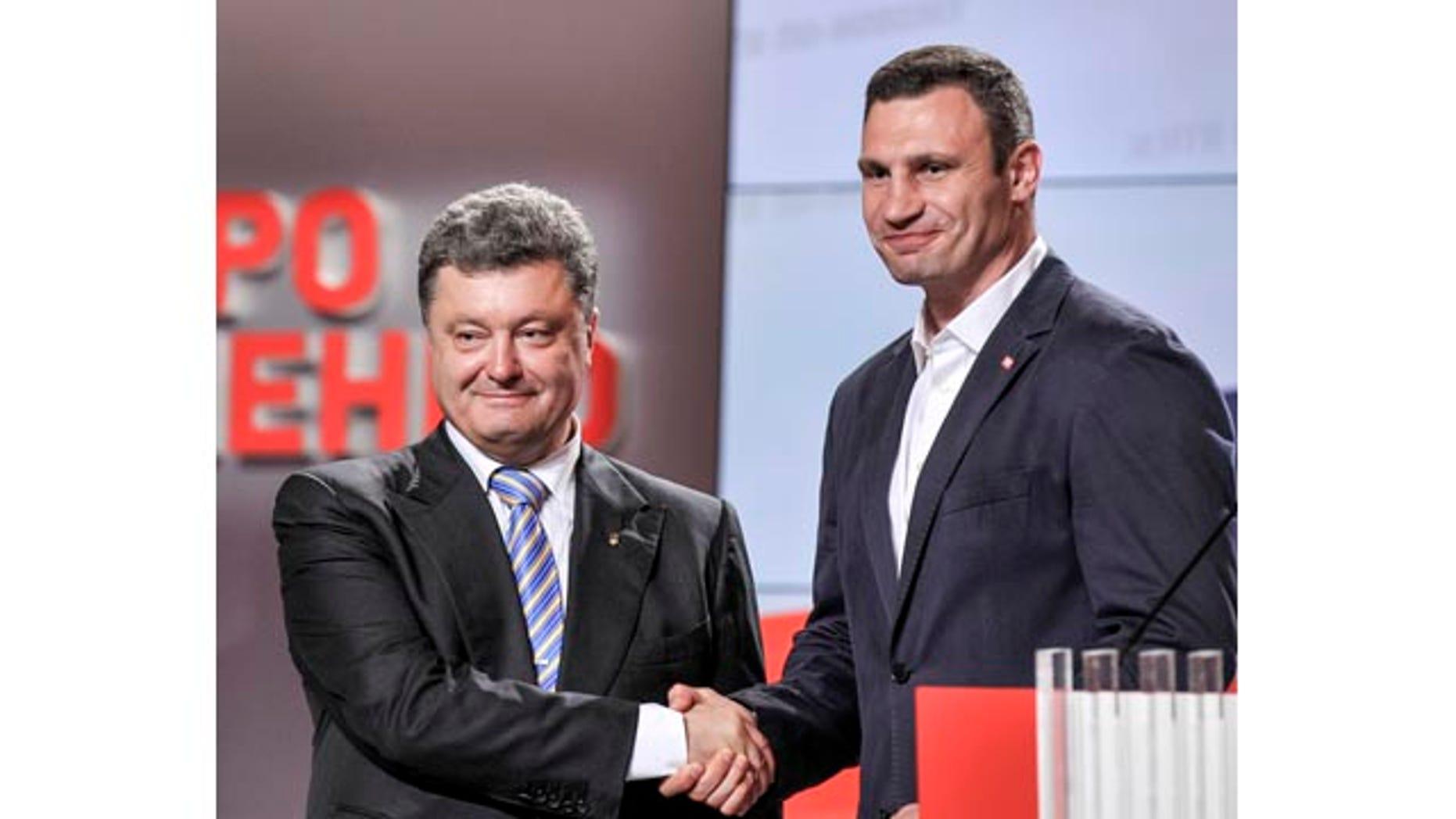 May 25, 2014: Ukrainian presidential candidate Petro Poroshenko, left, shake hands with Kiev mayoral candidate Vitali Klitschko during their press conference in Kiev. (AP Photo/Mykola Lazarenko, Pool)