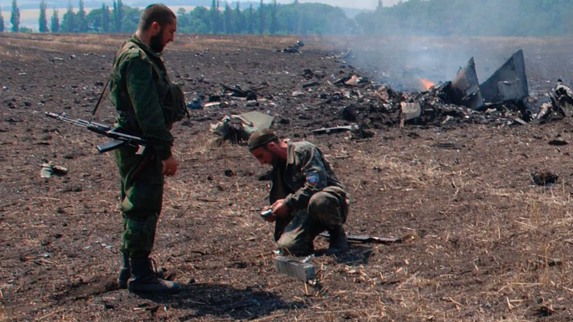 In this framegrab made from a video provided by press service of the rebel Donetsk People's Republic and icorpus.ru,  pro-Russians collect parts of the burning debris of a Ukrainian military fighter jet, shot down at Savur Mogila, eastern Ukraine, Wednesday, July 23, 2014. Two Ukrainian military Sukhoi-25 fighters have been shot down in the east, according to the country's Defense Ministry. (AP Photo/icorpus.ru, Press Service of the rebel Donetsk People's Republic)