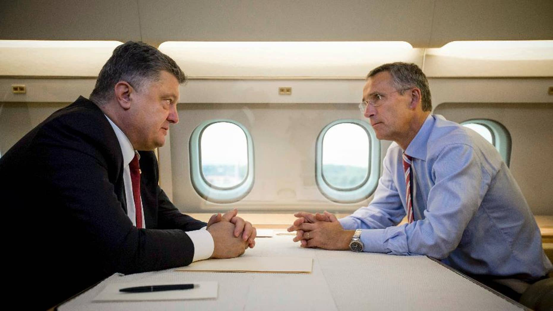Ukrainian President Petro Poroshenko, left, and NATO Secretary General Jens Stoltenberg talk in a helicopter on the way to a military training ground outside Lviv, western Ukraine, Monday, Sept. 21, 2015. Stoltenberg arrived in Ukraine for NATO-Ukraine joint exercises. (Mikhail Palinchak, Pool Photo via AP )