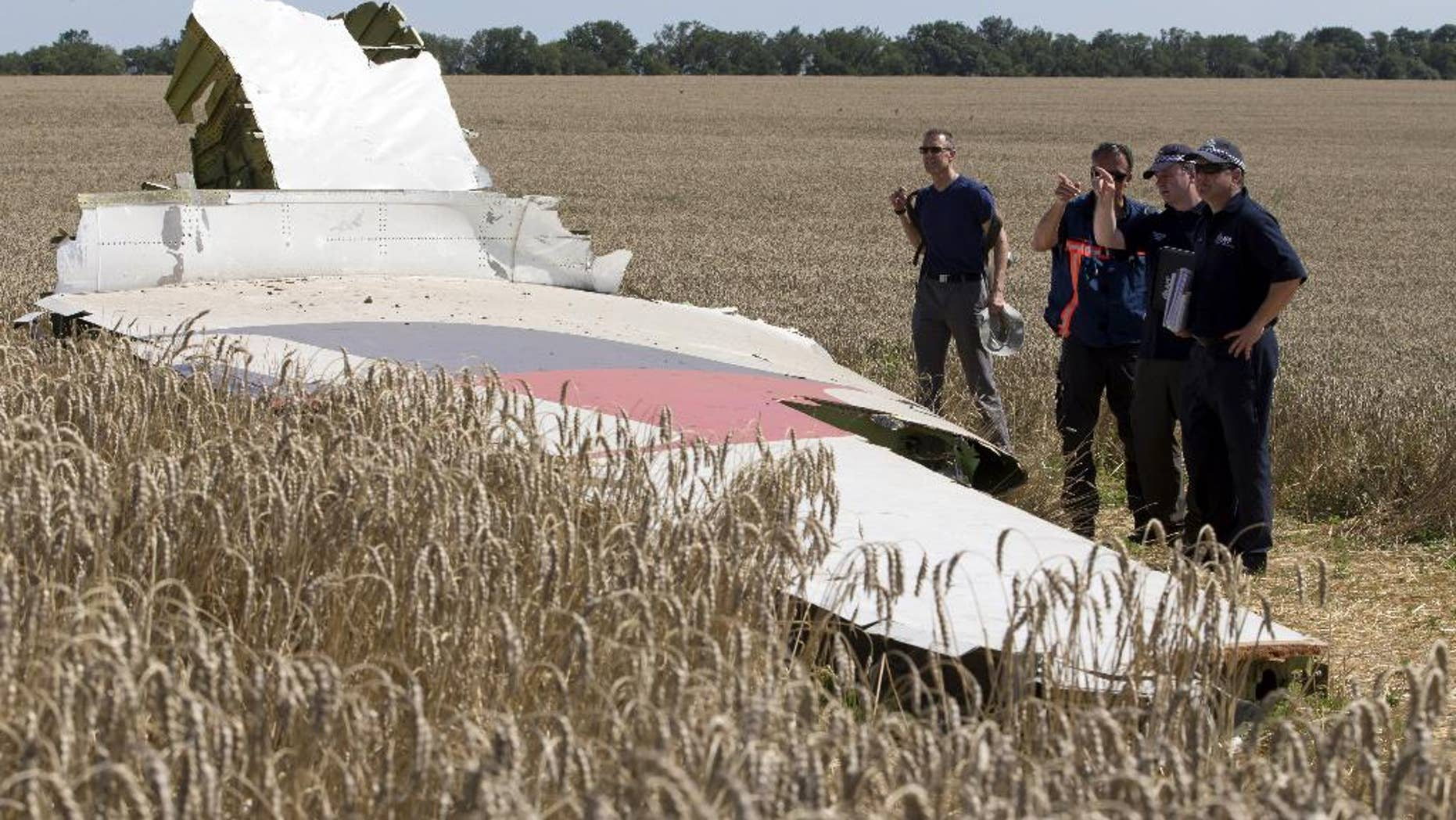 FILE - This Aug. 1, 2014 file photo shows investigators examining a piece of the Malaysia Airlines Flight 17 plane crash near the village of Hrabove, Donetsk region, eastern Ukraine. U.S. and international pilot unions are pressing the Obama administration and global aviation officials to get intelligence to airlines faster on potential threats to civil aviation from hostilities around the world following last month's shoot down of an airliner carrying nearly 300 people.  (AP Photo/Dmitry Lovetsky, File)
