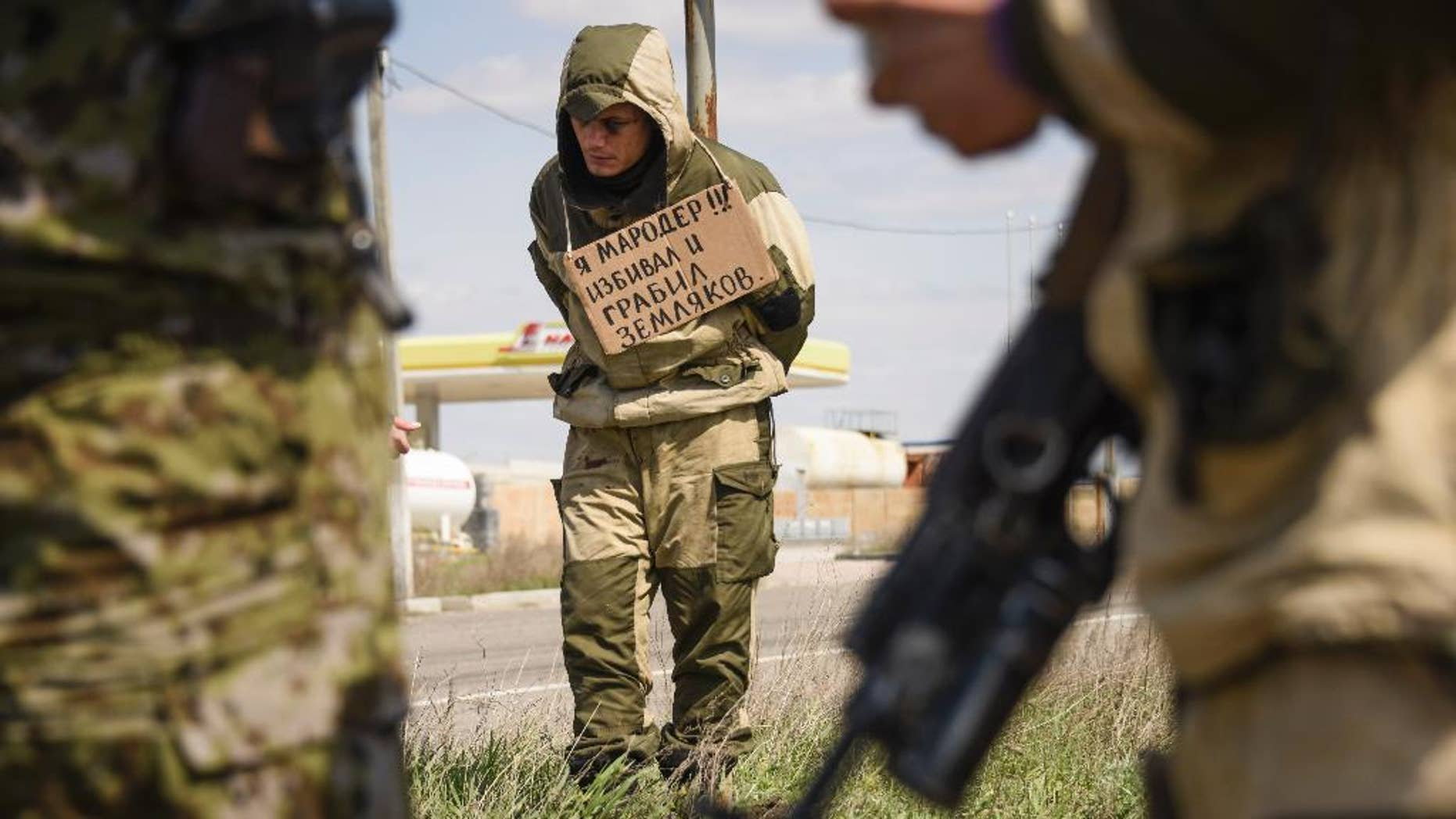 """A man stands tied to a post by pro-Russian rebels, accused of stealing from local people, with a poster around his neck reading  """"I am marauder, I beat and steal from civilians"""",  standing next to a highway in Krasnyi Partyzan, Ukraine, Thursday, April 23, 2015. (AP Photo/Mstyslav Chernov)"""