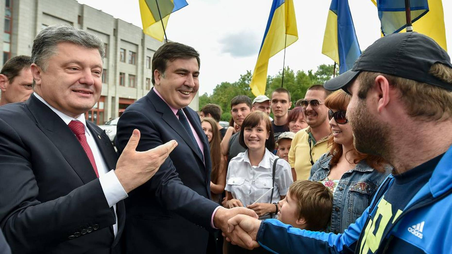 Citizens greet Ukrainian President Petro Poroshenko, left, and Mikhail Saakashvili, second left, a newly appointed governor of Odessa region, in Odessa, Ukraine, Saturday, May 30, 2015. Former Georgian President Mikhail Saakashvili on Saturday was appointed governor of Ukraine's troubled south-west Odessa region. (AP Photo/Mykola Lazarenko, Presidential Press Service Pool Photo via AP)