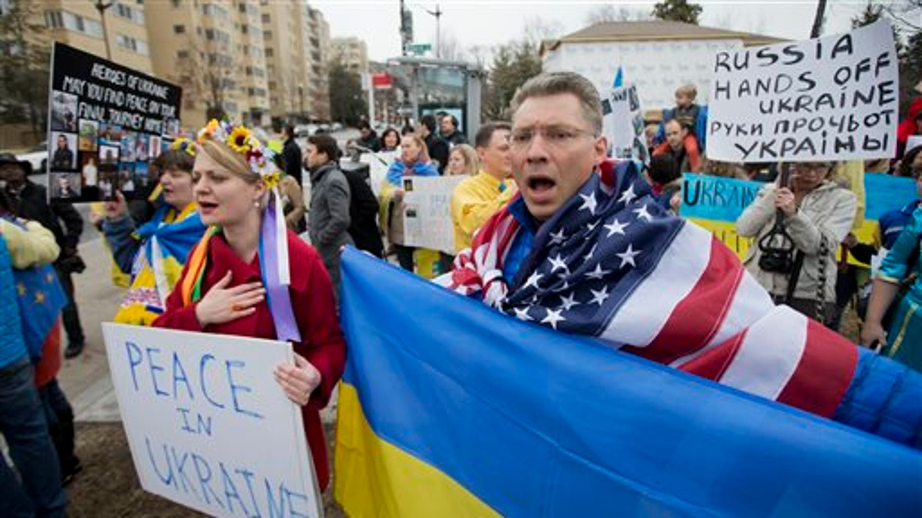 "Moscow-born Dmitry Savransky, right, who holds dual citizenship, American and Russian, joins his Ukrainian wife Natalya Seay, left, during a protest rally in front of the Russian embassy, in Washington, Sunday, March 2, 2014. Igniting a tense standoff, Russian forces surrounded a Ukrainian army base Sunday just as the country began mobilizing in response to the surprise Russian takeover of Crimea. Outrage over Russia's tactics mounted in world capitals, with U.S. Secretary of State John Kerry calling on President Vladimir Putin to pull back from ""an incredible act of aggression."" (AP Photo/Manuel Balce Ceneta)"