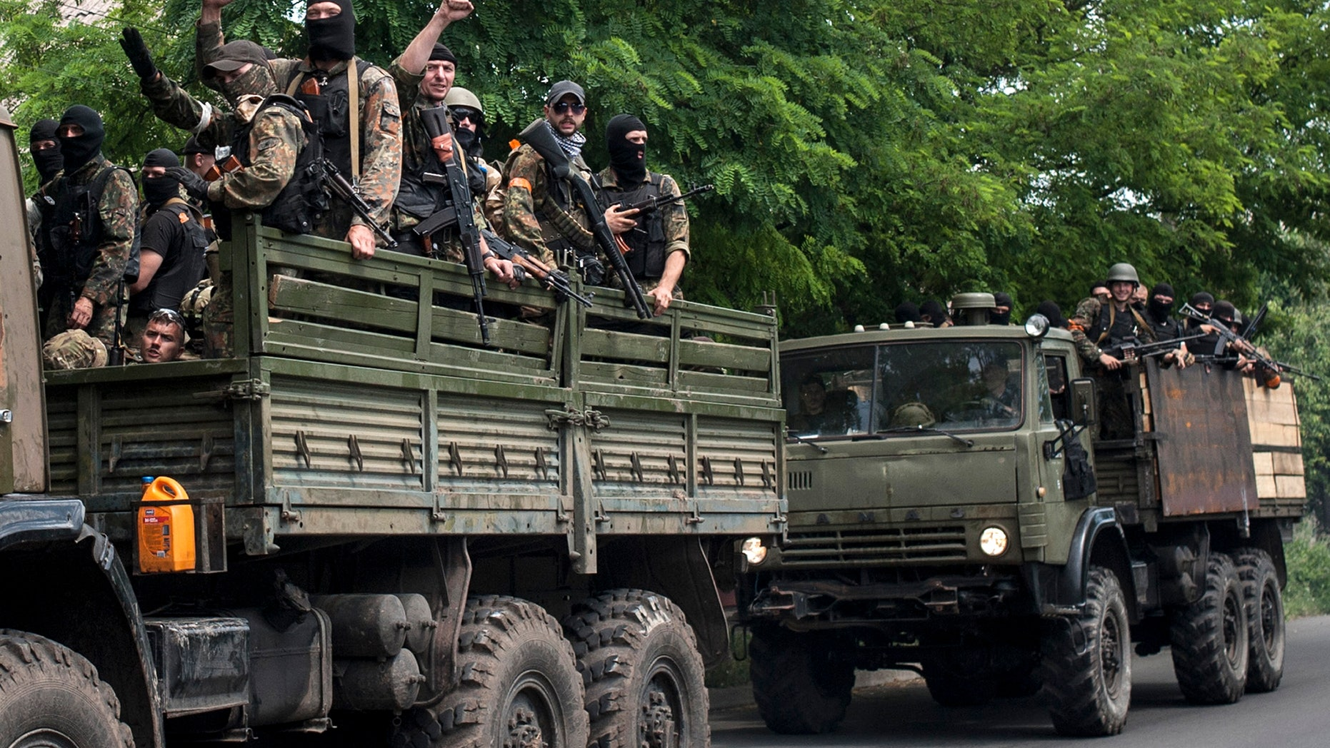 June 13, 2014 - Ukrainian troops stand atop vehicles as they leave a site of a battle in Mariupol, eastern Ukraine. Ukraine's interior minister says government troops attacked pro-Russian separatists in the southern port of Mariupol.
