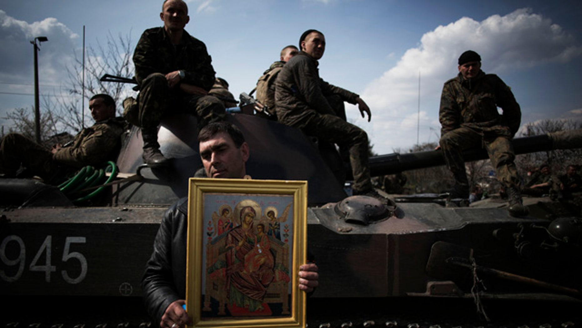 April 16, 2014: A local resident holds an Orthodox icon in front of an armored vehicle and soldiers of the Ukrainian Army, as they are blocked by people on their way to the town of Kramatorsk. Pro-Russian insurgents commandeered six Ukrainian armored vehicles along with their crews and hoisted Russian flags over them Wednesday, dampening the central government's hopes of re-establishing control over restive eastern Ukraine. (AP Photo/Manu Brabo)