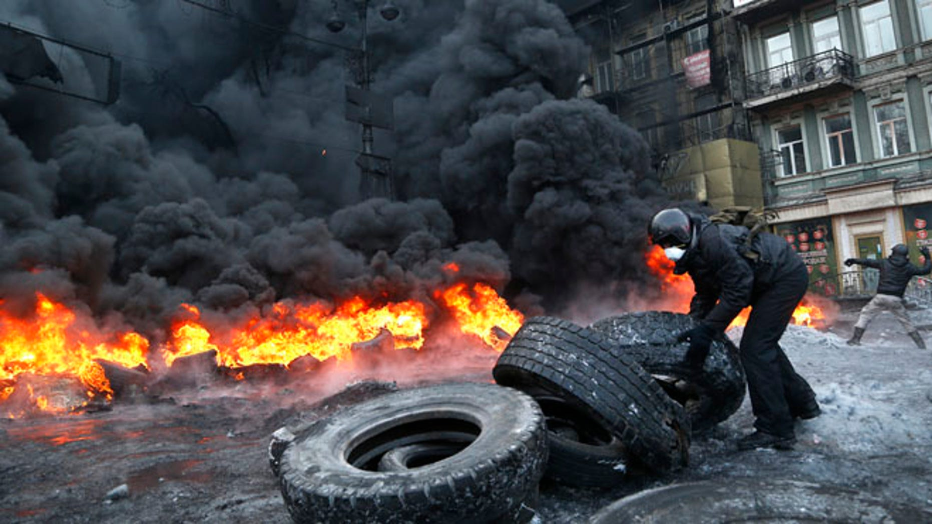Jan. 25, 2014: A protester prepares to throw a tire onto a fire during clashes with police in central Kiev, Ukraine, early Saturday.